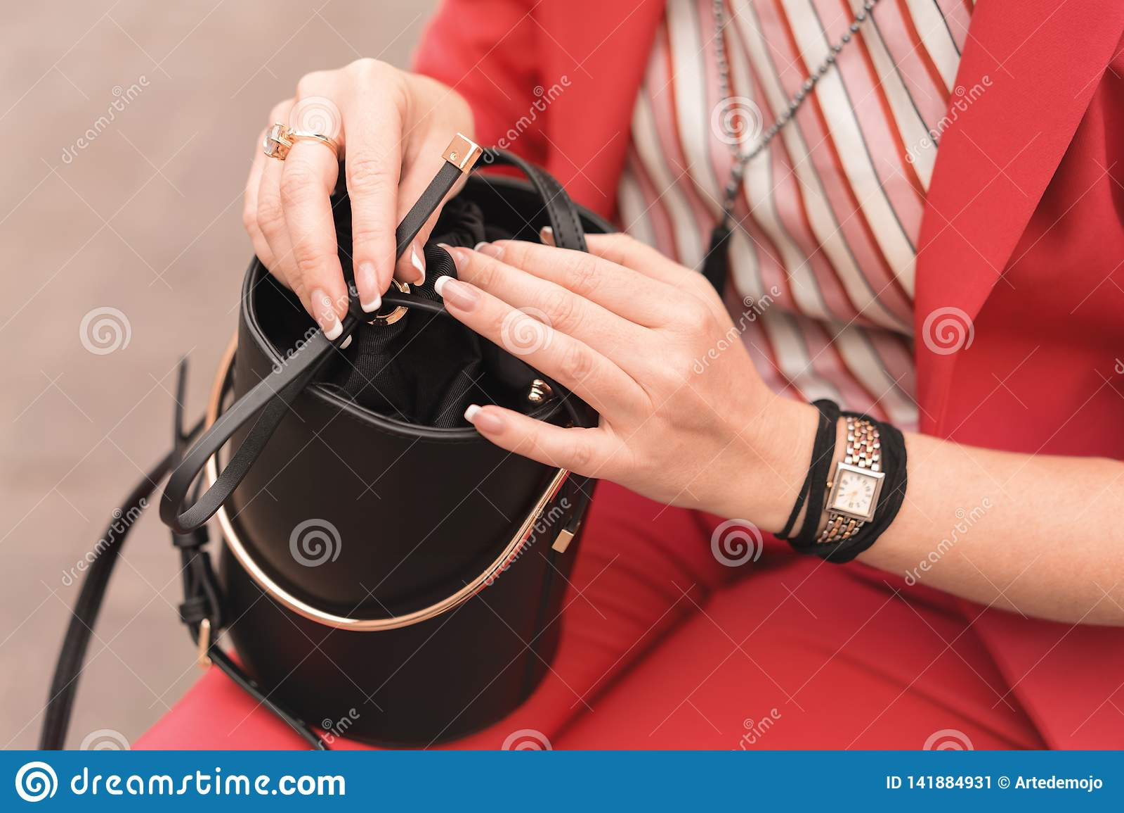 Eine Frau in der modernen Kleidung der Farbe der lebenden korallenroten Griffe des Jahres 2019 in den Händen mit französischer Ma