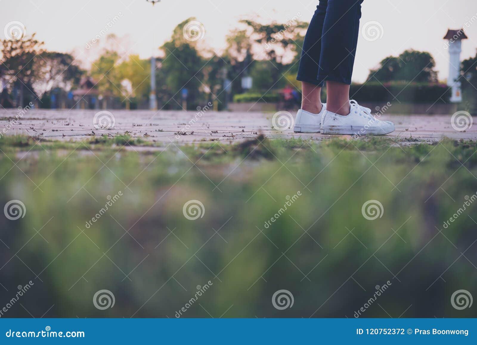 Eine Frau, die auf der Brücke mit dem Fühlen traurig sitzt