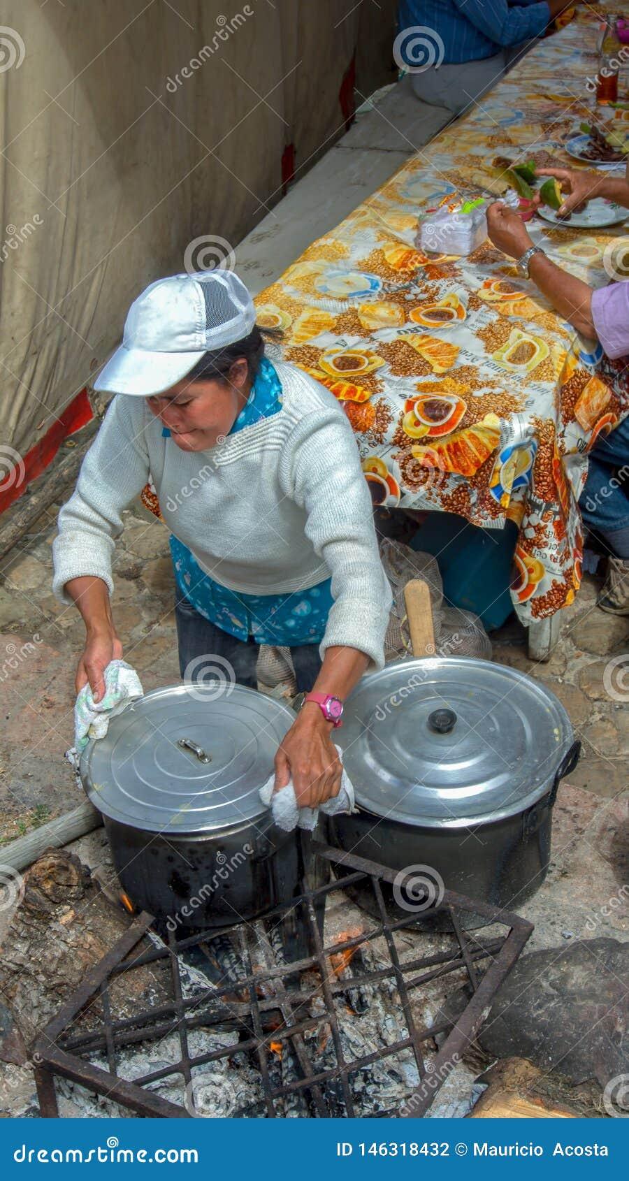 Eine Frau, die auf einem hölzernen Feuer kocht