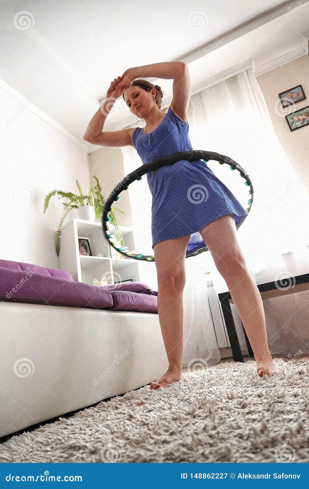 Eine Frau dreht ein hula Band zu Hause Selbsttraining mit einem Band