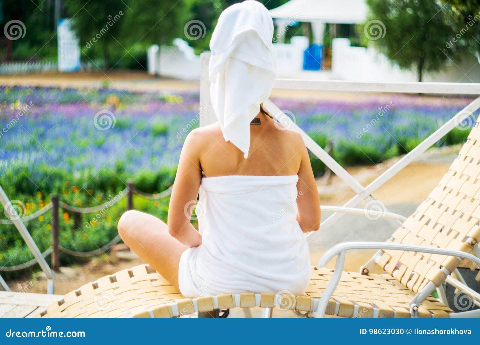 Eine Frau in einem Badtuch sitzt auf einem Aufenthaltsraum auf einer Terrasse