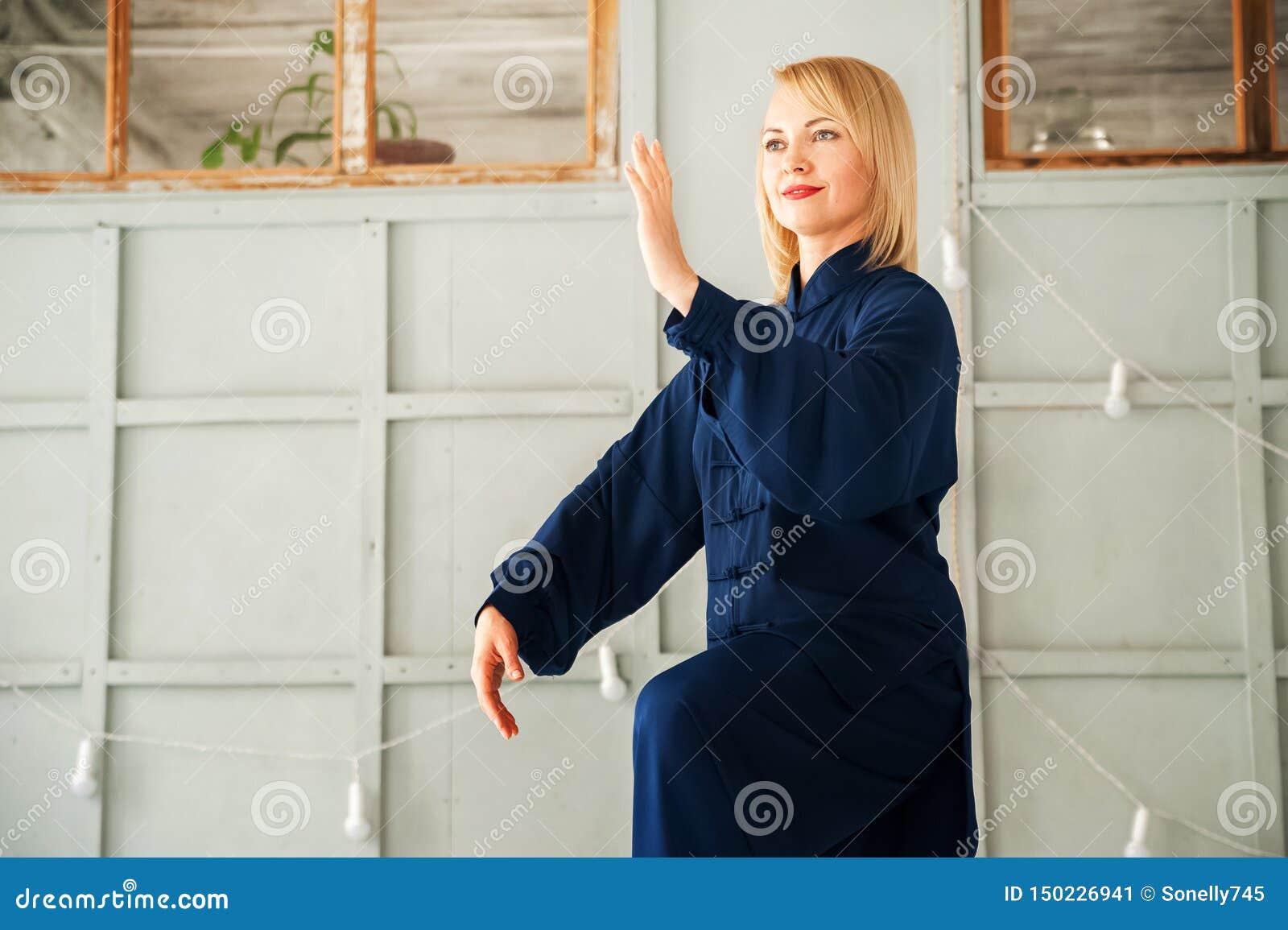 Eine Frau in einem blauen Kimono nimmt an chinesischer Kampfkunst Tai Chi-Nahaufnahme und Kopienraum teil