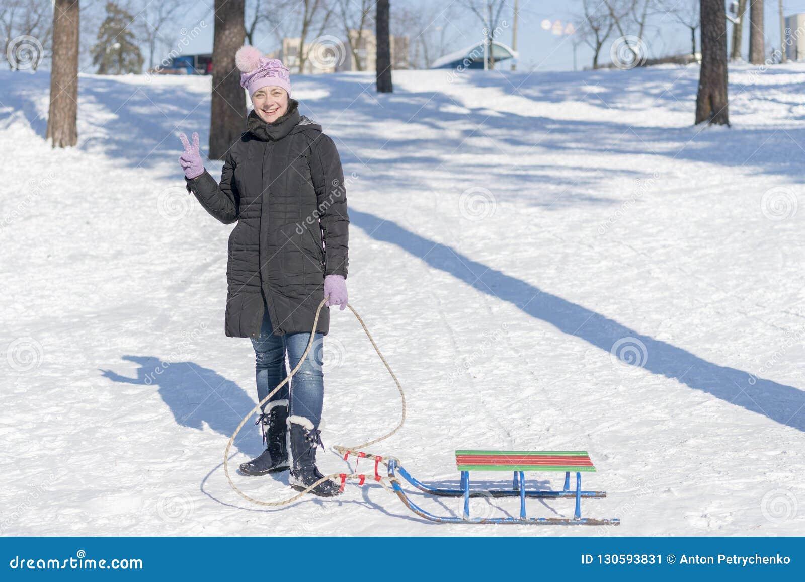 Eine Frau in einer schwarzen Winterjacke mit Schlitten in einem schneebedeckten Park oder in einem Wald