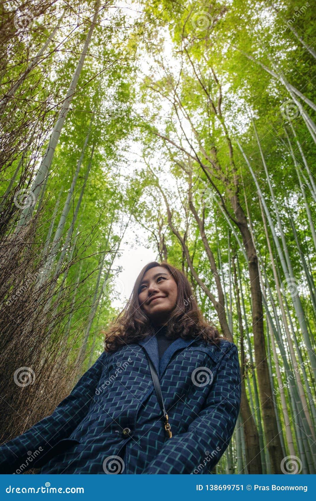 Eine Frau mit Bambuswald im Hintergrund