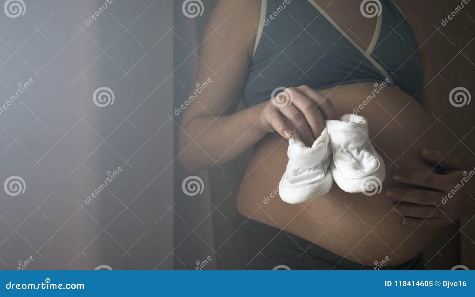 Eine Frau am 9. Monat der Schwangerschaft hält in ihren Handpantoffeln für ein neugeborenes Baby