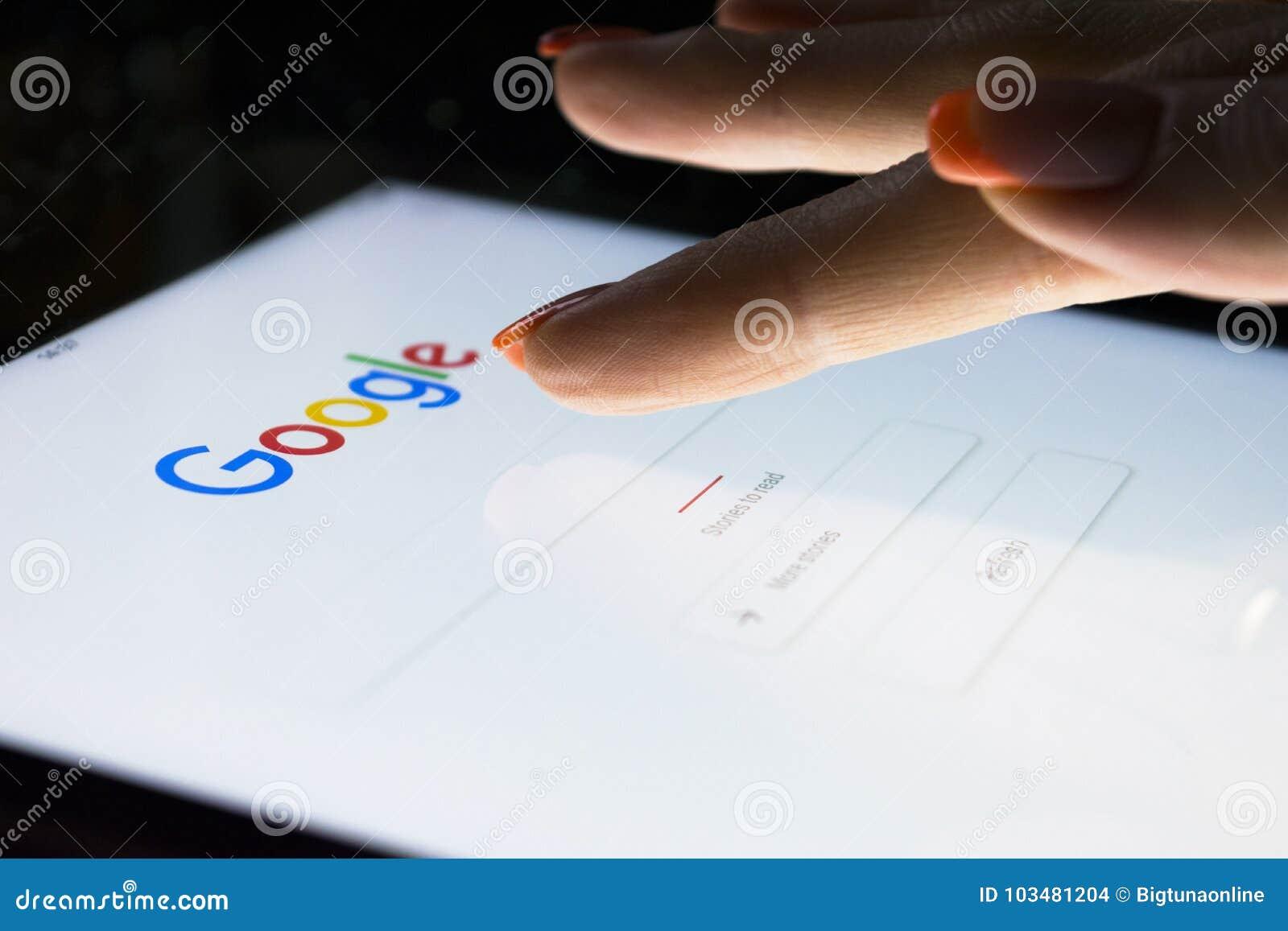 Eine Frau ` s Hand ist Touch Screen auf Tablet-Computer iPad, das nachts für das Suchen auf Google-Suchmaschine Pro ist Google is