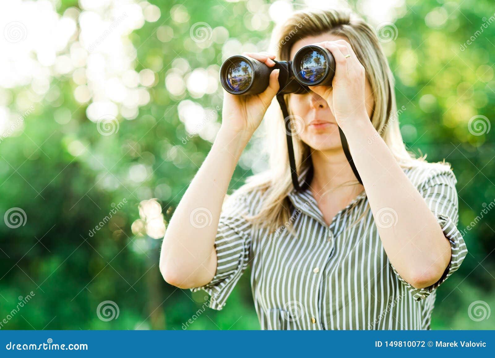 Eine Frau schaut durch die Ferngläser, die im Wald im Freien sind