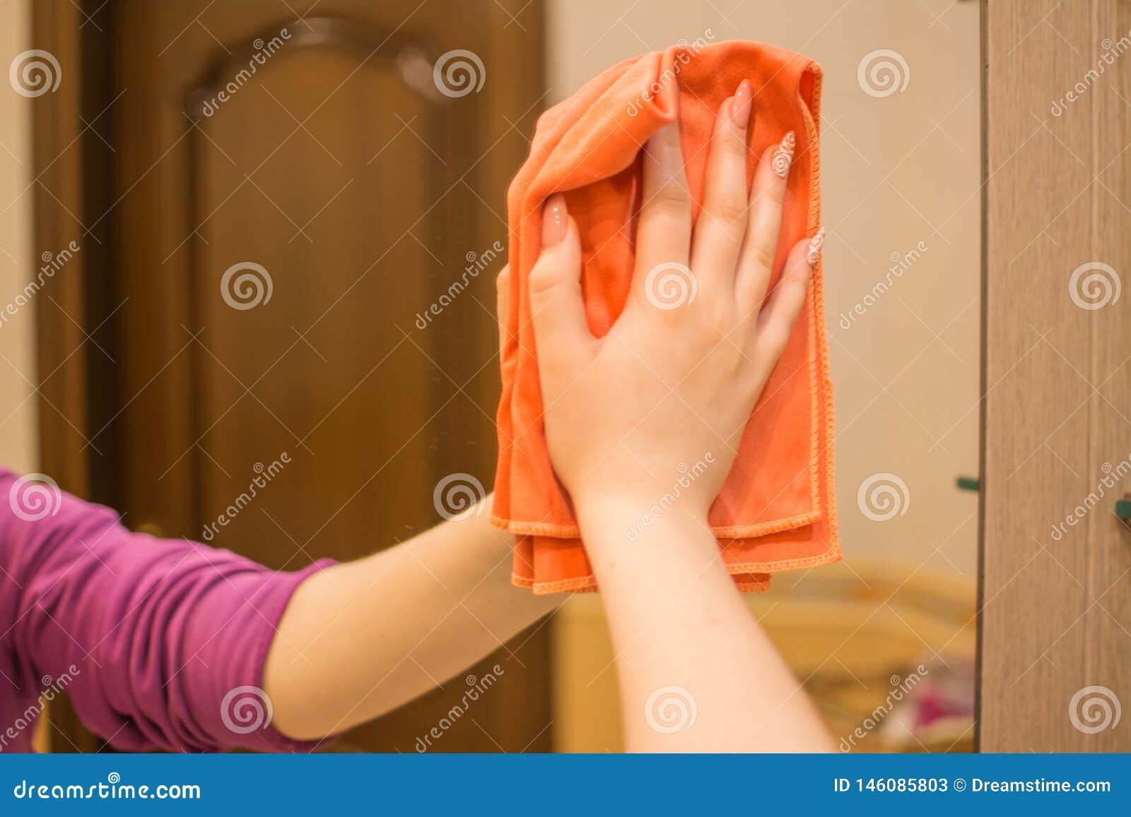 Eine Frau wäscht einen Spiegel mit einem speziellen Lappen
