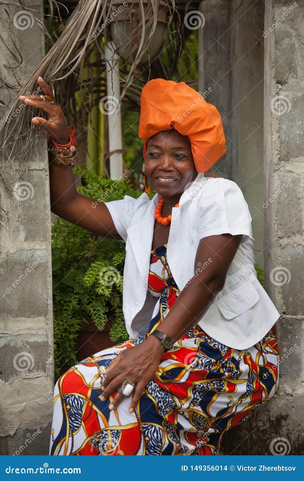 Eine frohe afro-amerikanische Frau, die ein helles buntes Nationalkost?m tr?gt, sitzt in der ?ffnung eines Ziegelstein Gazebo
