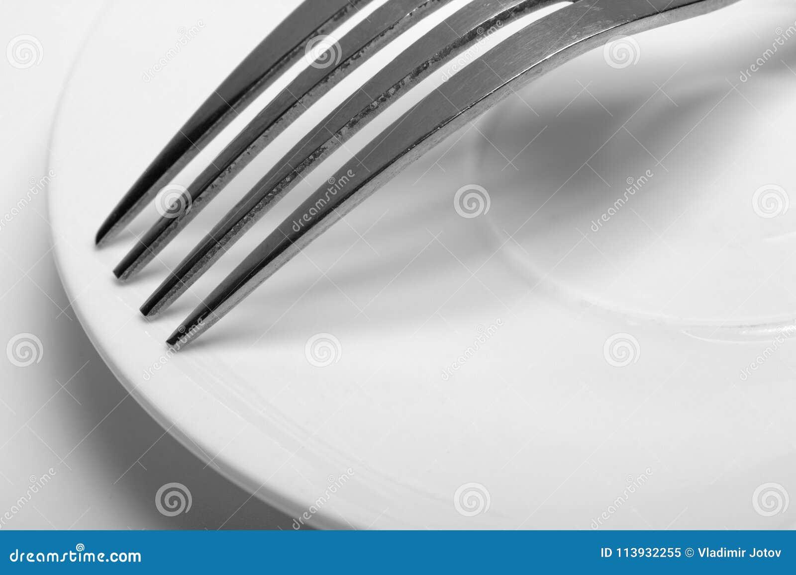 Eine Gabel auf einem Teller Nahaufnahme auf weißem Hintergrund