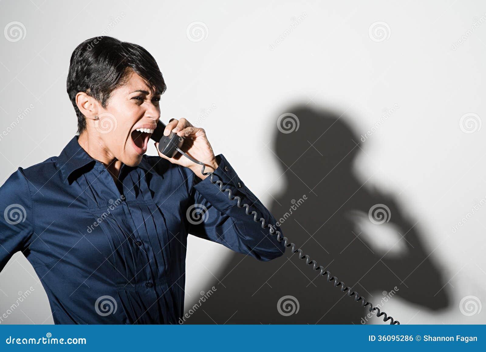Eine Geschäftsfrau, die am Telefon schreit