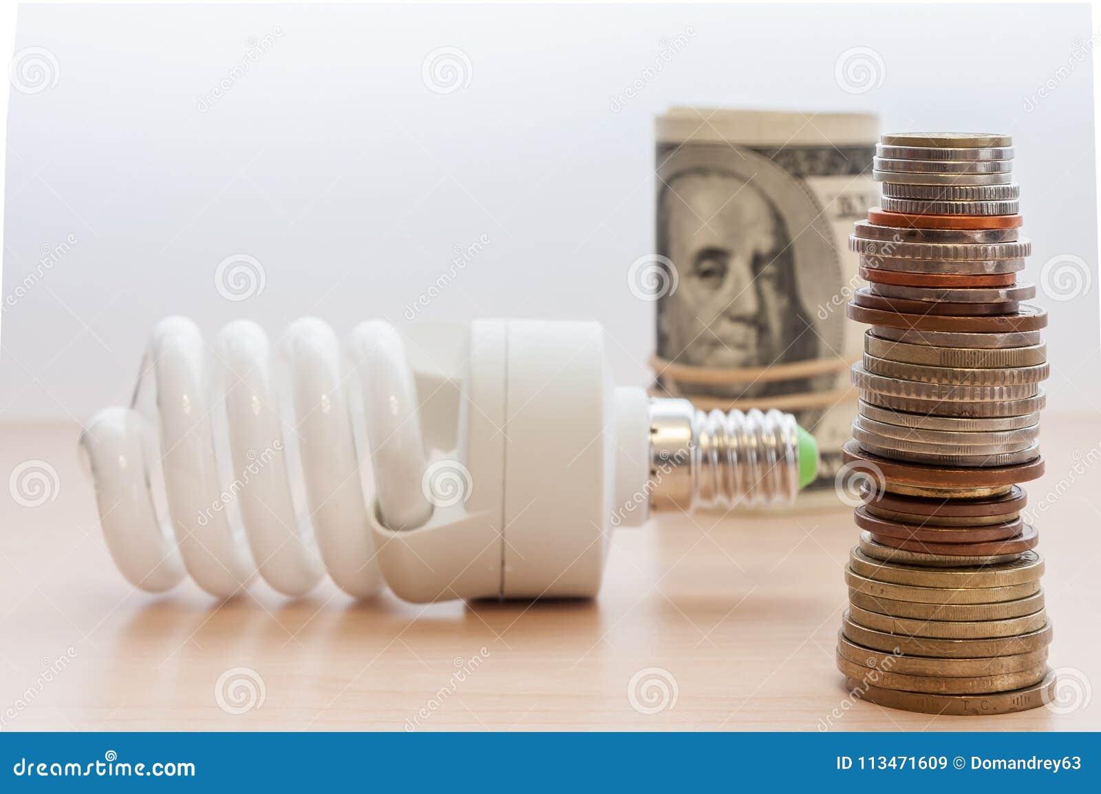 Eine Glühlampe, ein hoher Stapel Münzen von verschiedenen Ländern und dignities und Rechnungen falteten sich in ein Bündel