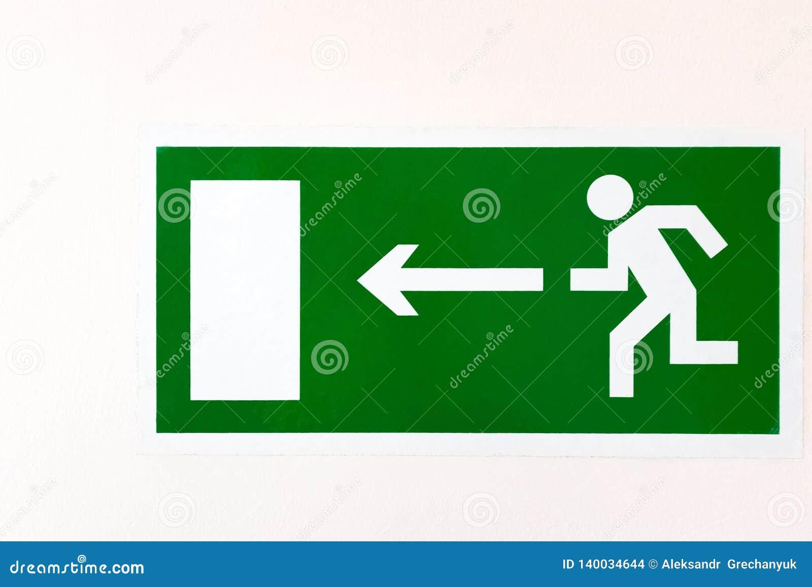 Eine grüne Plakat RICHTUNG NACH LINKS EVAKUIERUNGS-AUSGANG