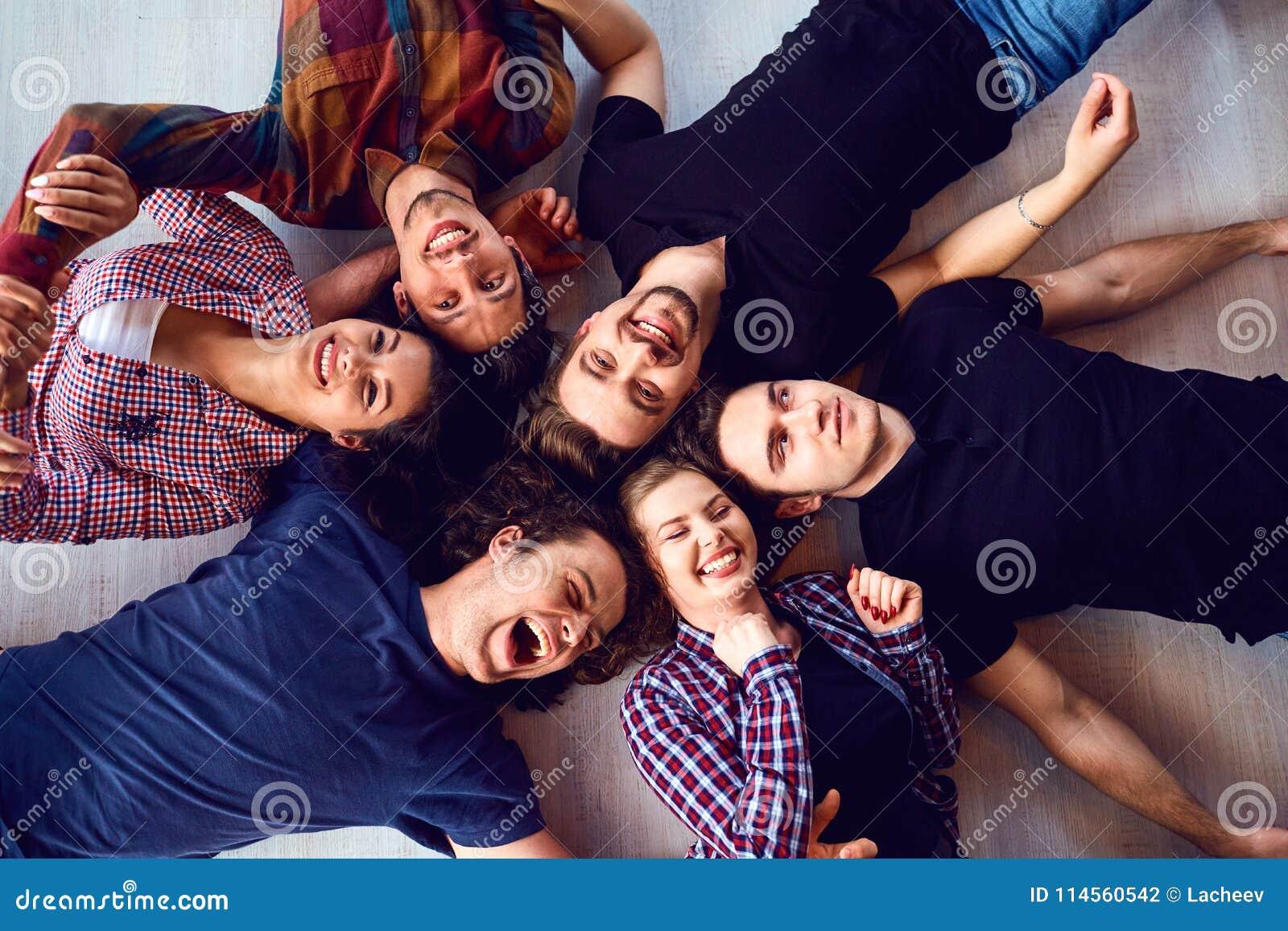 Eine Gruppe Freunde lachen das Lügen auf dem Boden im Raum