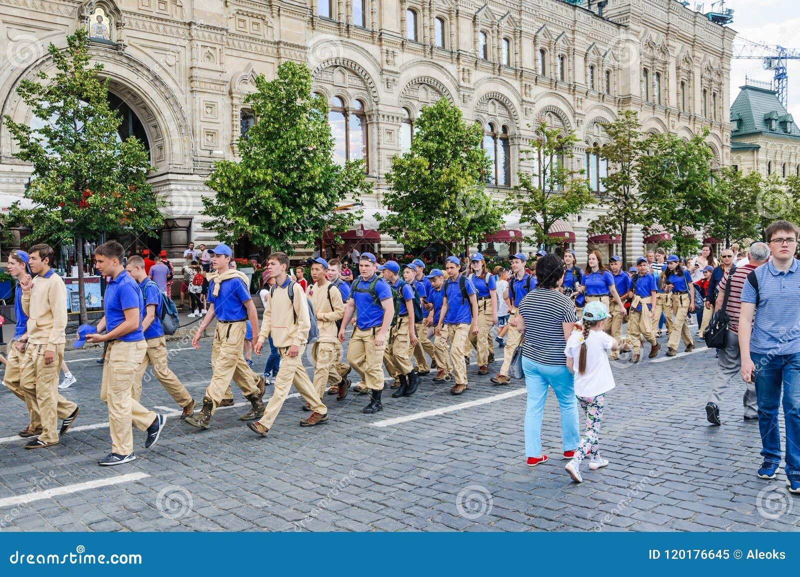 Eine Gruppe Jugendlichtouristen in der Uniform des Sommerlagers gehen in Paare auf dem roten Quadrat