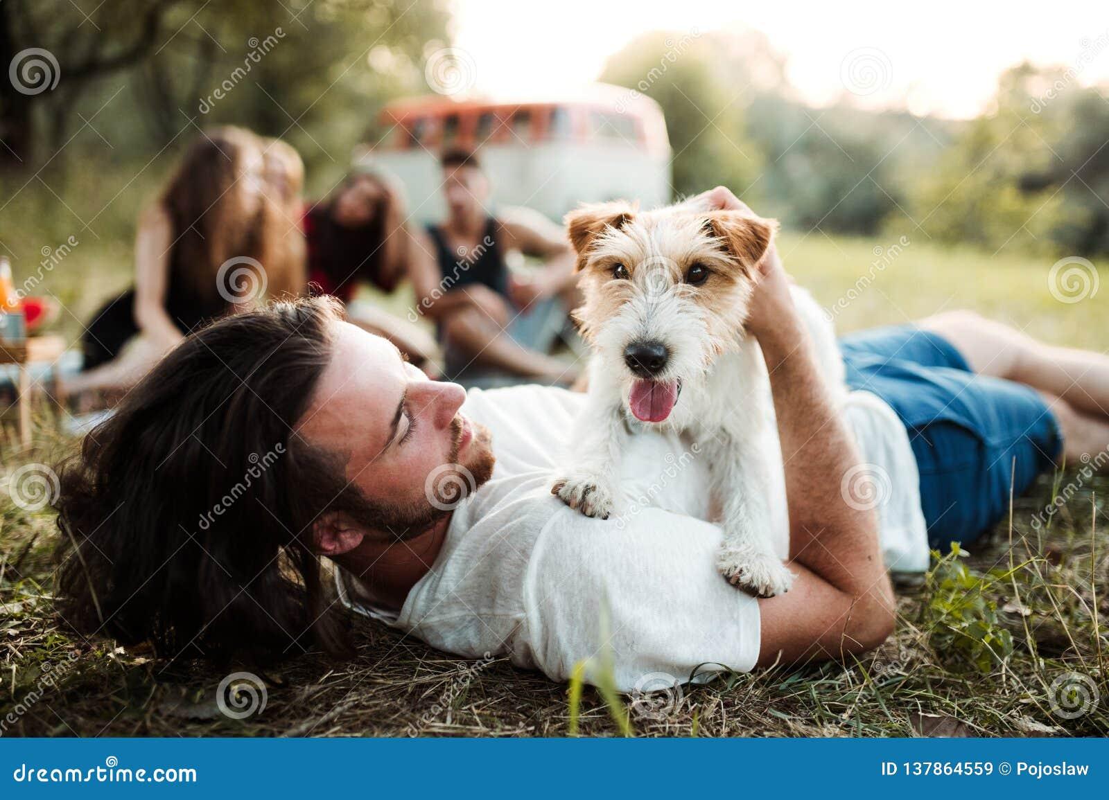Eine Gruppe junge Freunde mit einem Hund, der auf Gras auf einem roadtrip durch Landschaft sitzt