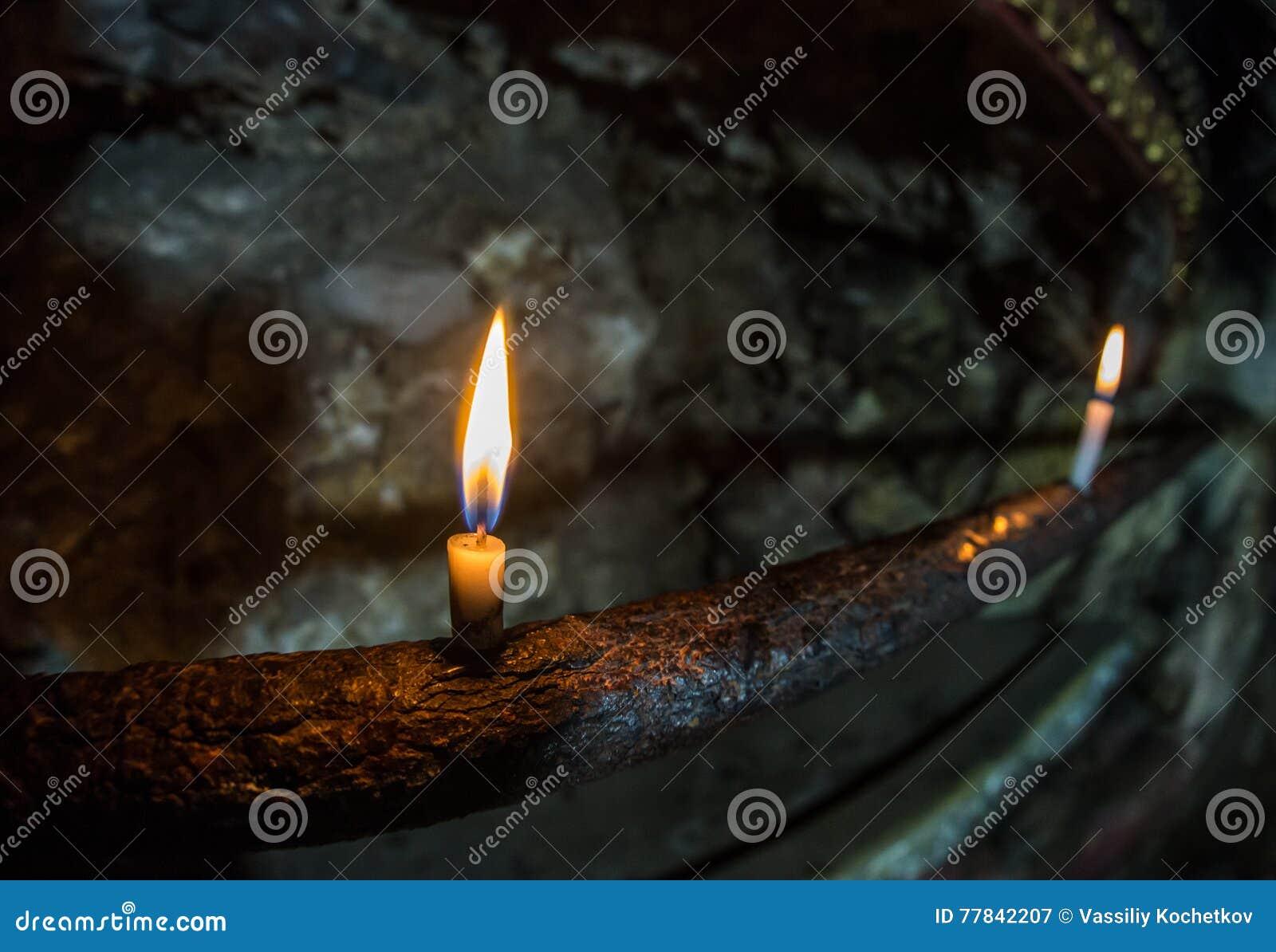 Eine helle Kerze, die hell im schwarzen Hintergrund brennt