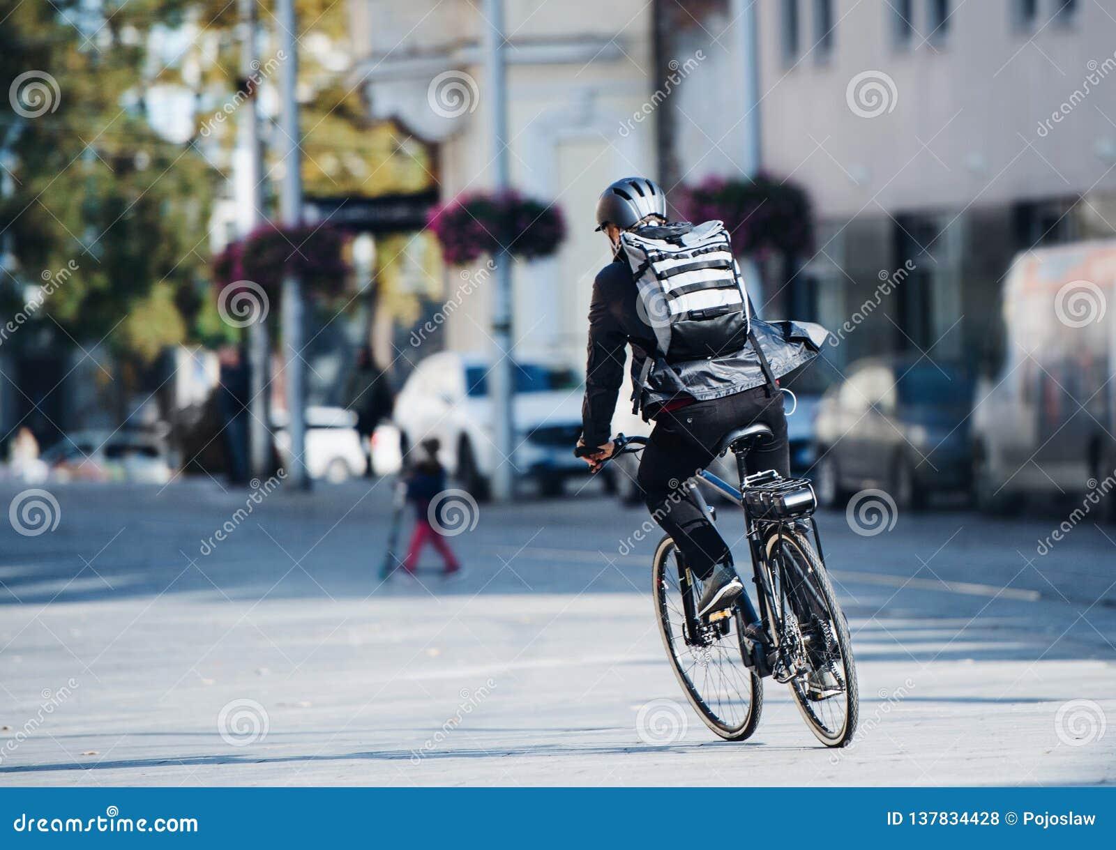 Eine hintere Ansicht des männlichen Fahrradkuriers, der Pakete in der Stadt liefert Kopieren Sie Platz