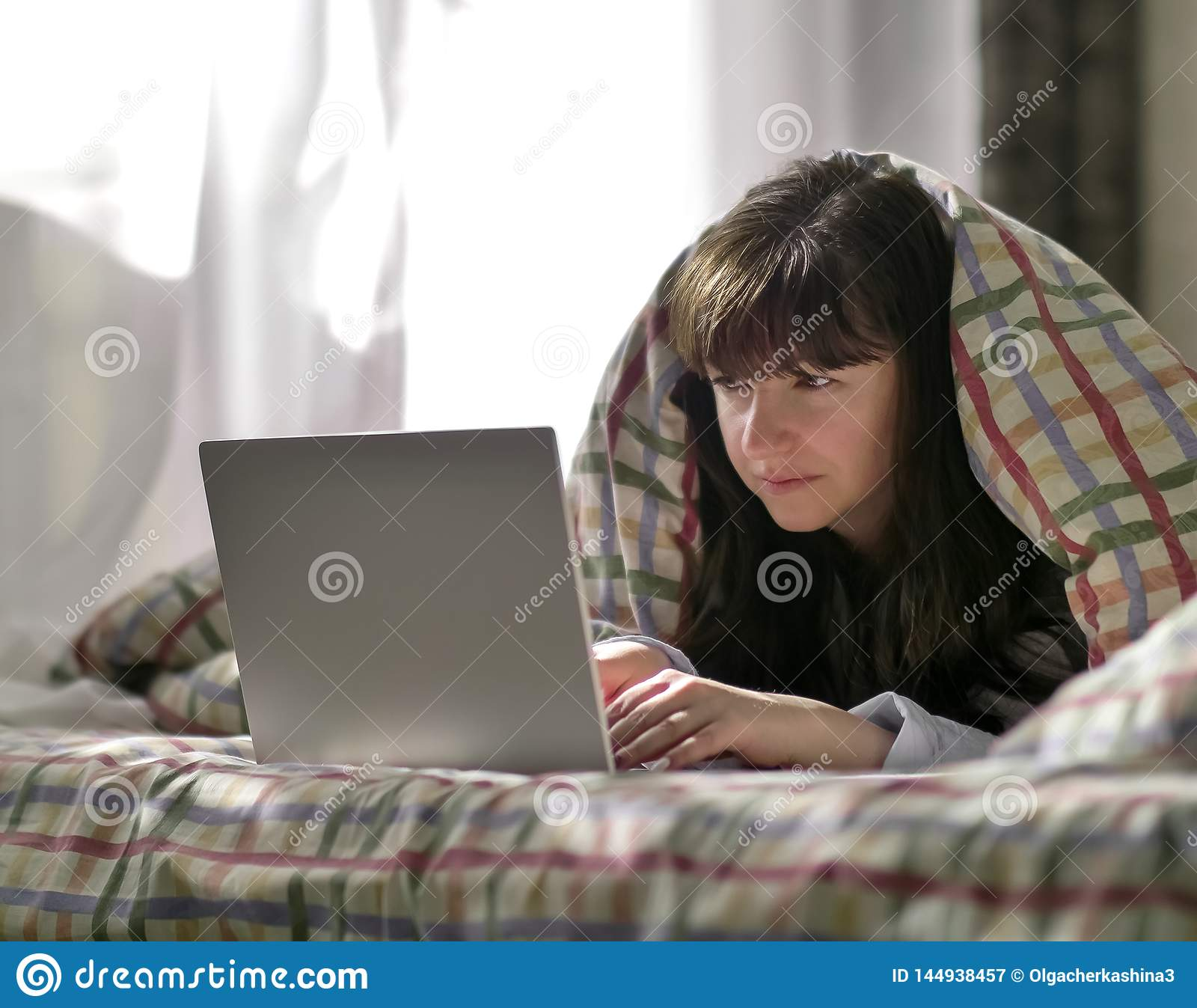 Eine junge brunette Frau liegt unter einer Decke und schreibt in einem Laptop