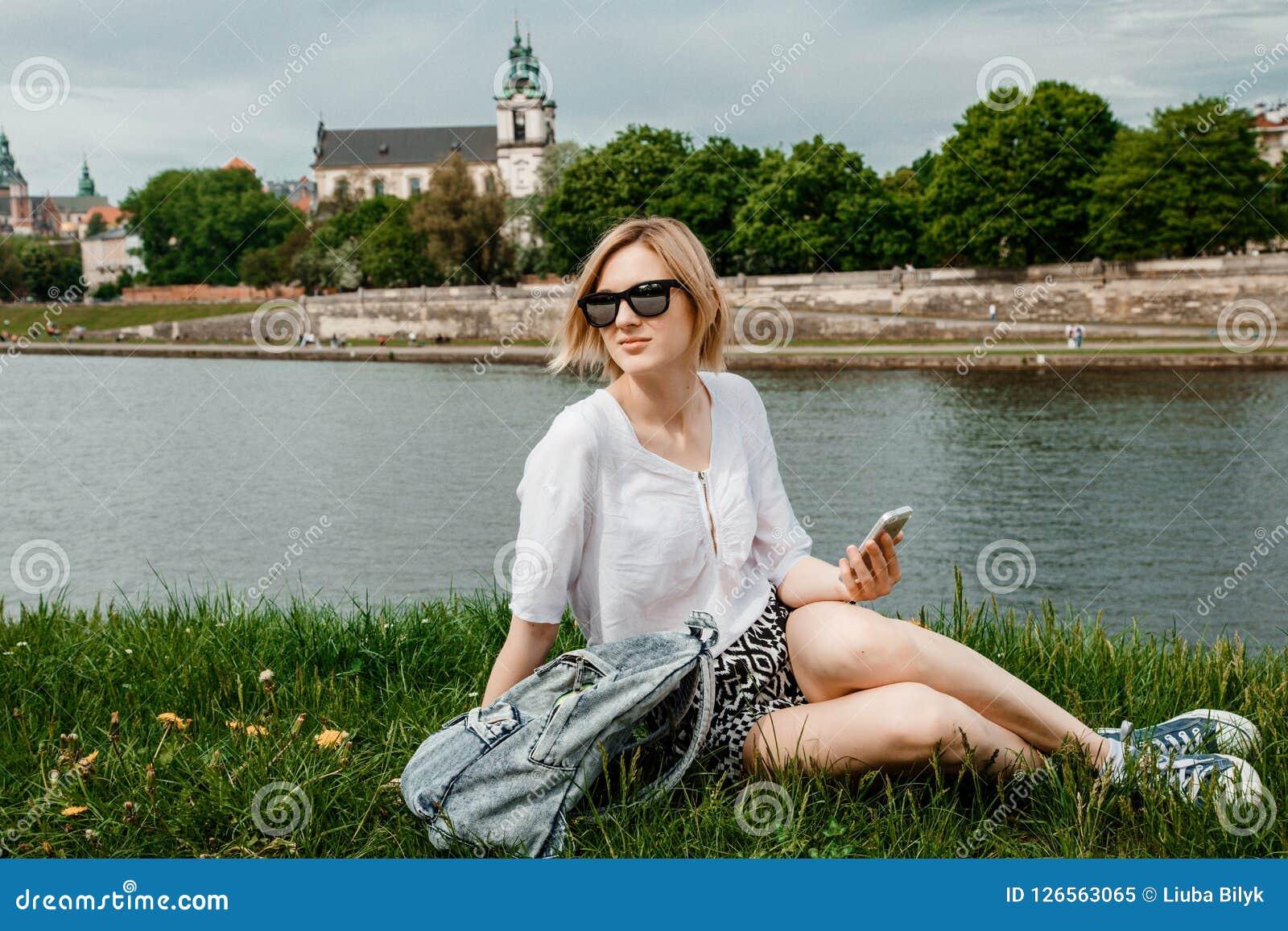 Eine junge Frau auf der Weichsel in Krakau Stilvolles Mädchen in der Sonnenbrille spricht an ihrem Telefon Ansicht der Stadt von