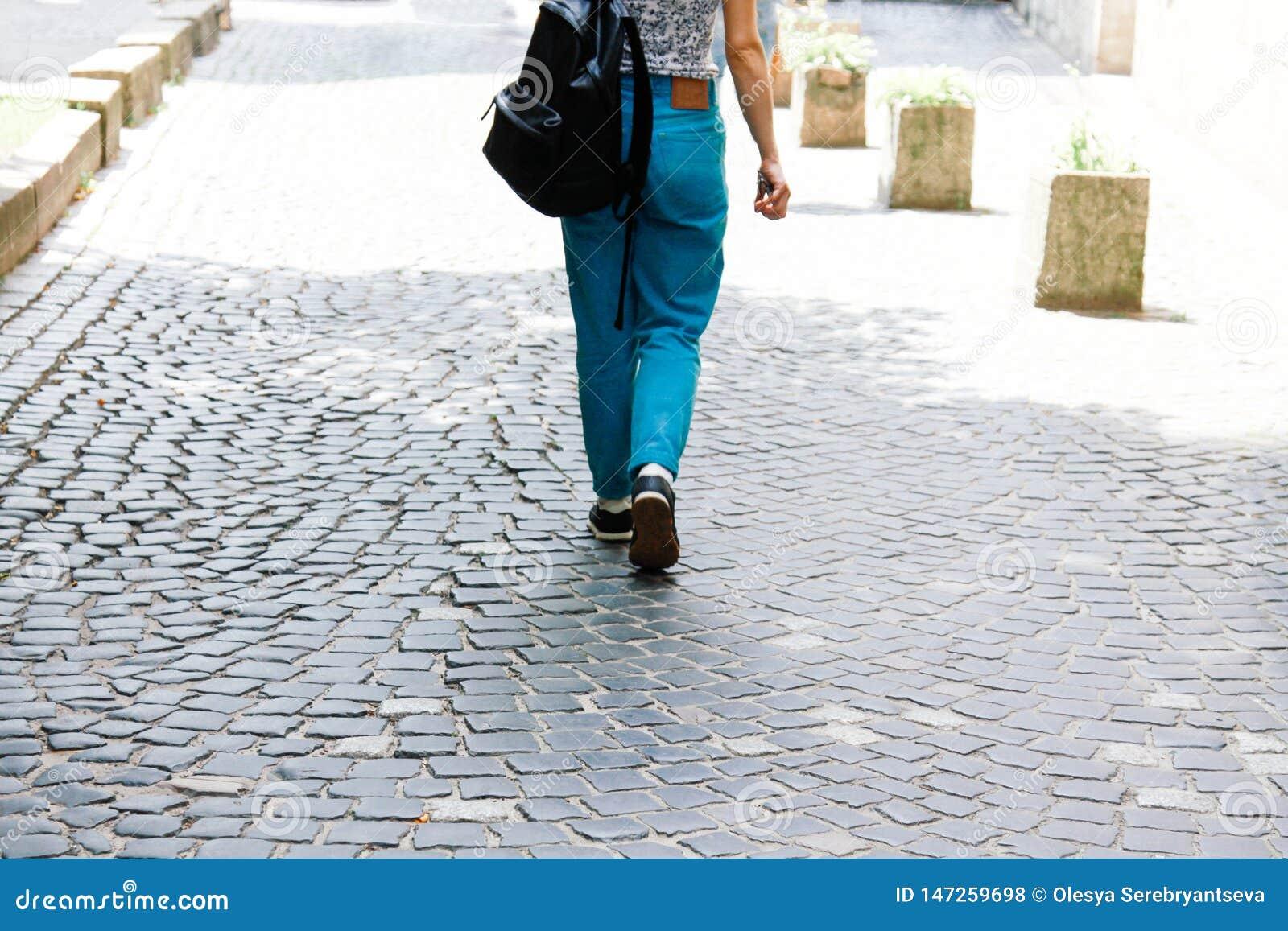 Eine junge Frau in der zufälligen Kleidung und in einem Rucksack geht hinunter die Straße Eine Frau schaut von der Rückseite Somm