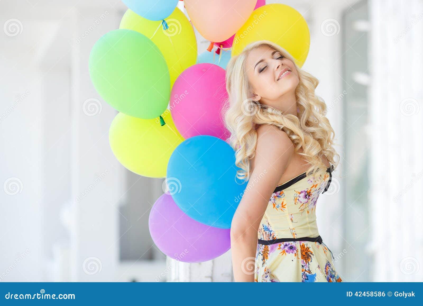 Eine junge Frau mit großem buntem Latex steigt im Ballon auf
