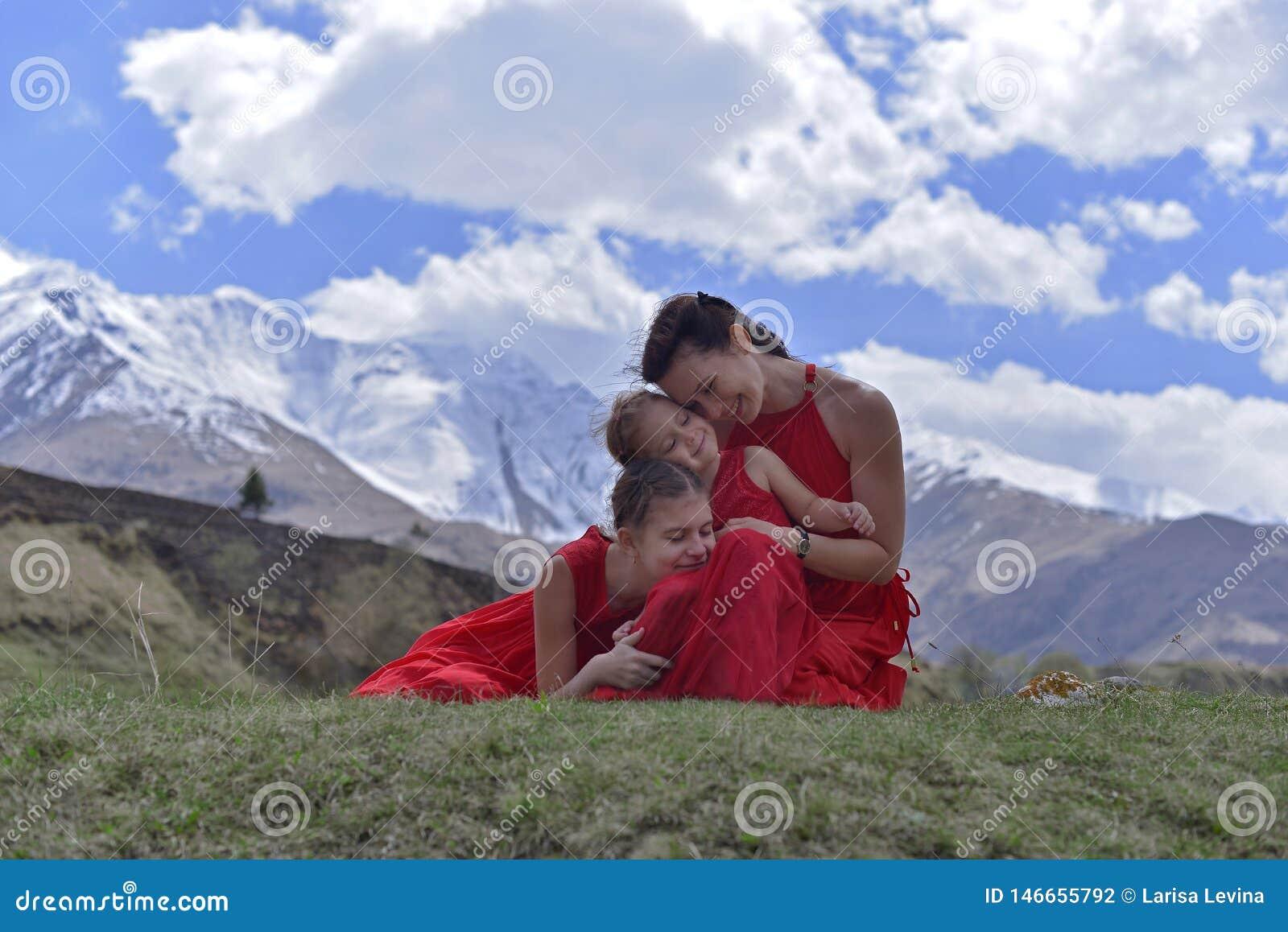 Eine junge Frau mit zwei T?chtern in den roten Kleidern, die im Fr?hjahr in den Schnee-mit einer Kappe bedeckten Bergen stillsteh
