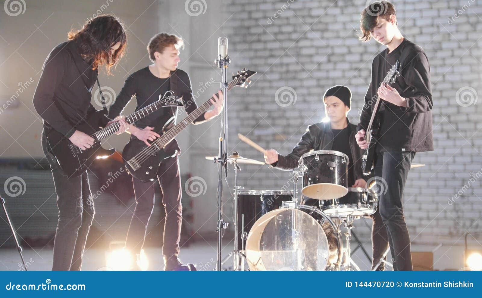 Eine junge Rockgruppe, die eine Wiederholung in einer Garage hat Mitglieder einer Gruppe, die schwarze Kleidung trägt Helle Beleu
