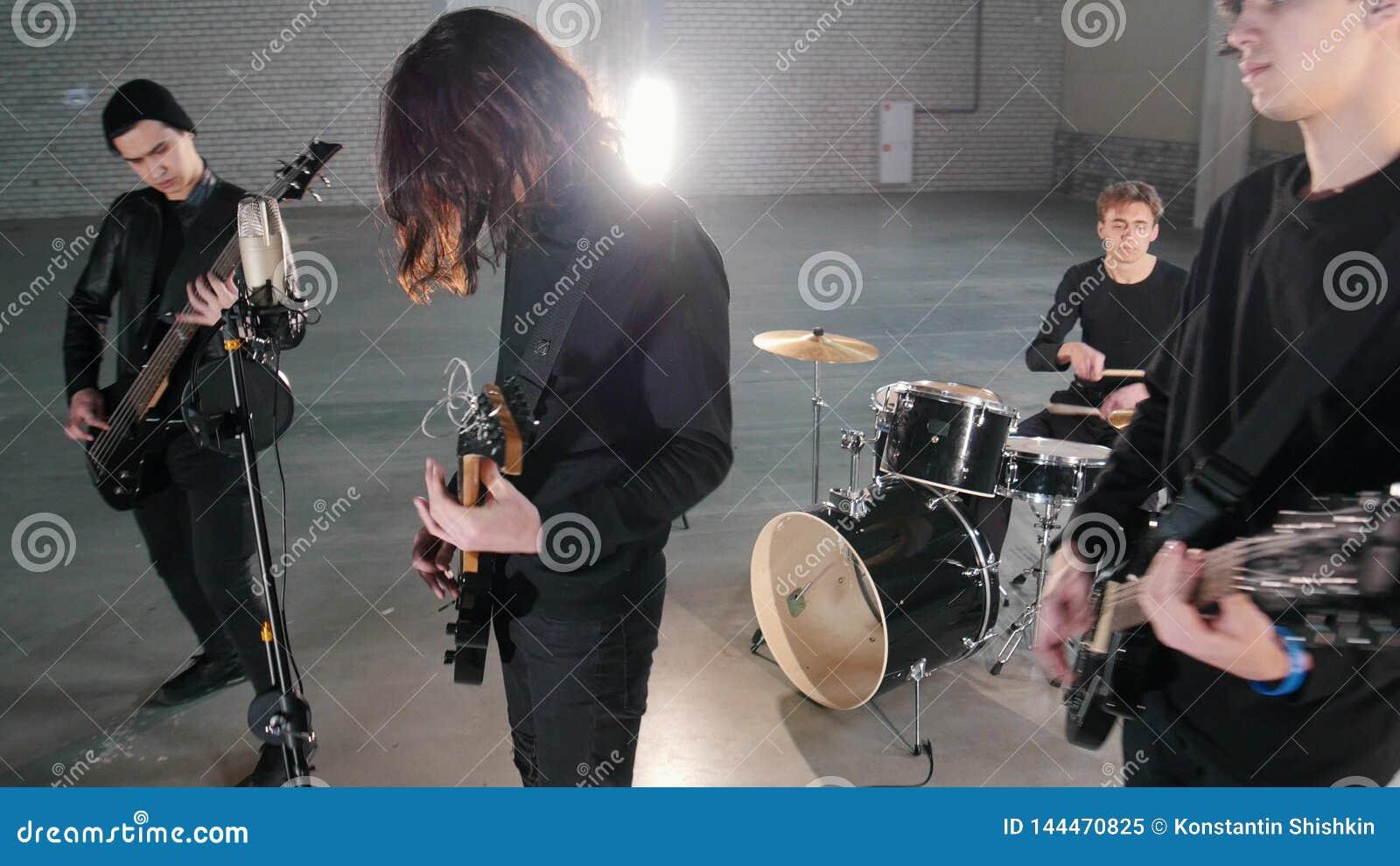 Eine junge Rockgruppe, die eine Wiederholung in einer Garage hat Mitglieder einer Gruppe, die schwarze Kleidung trägt