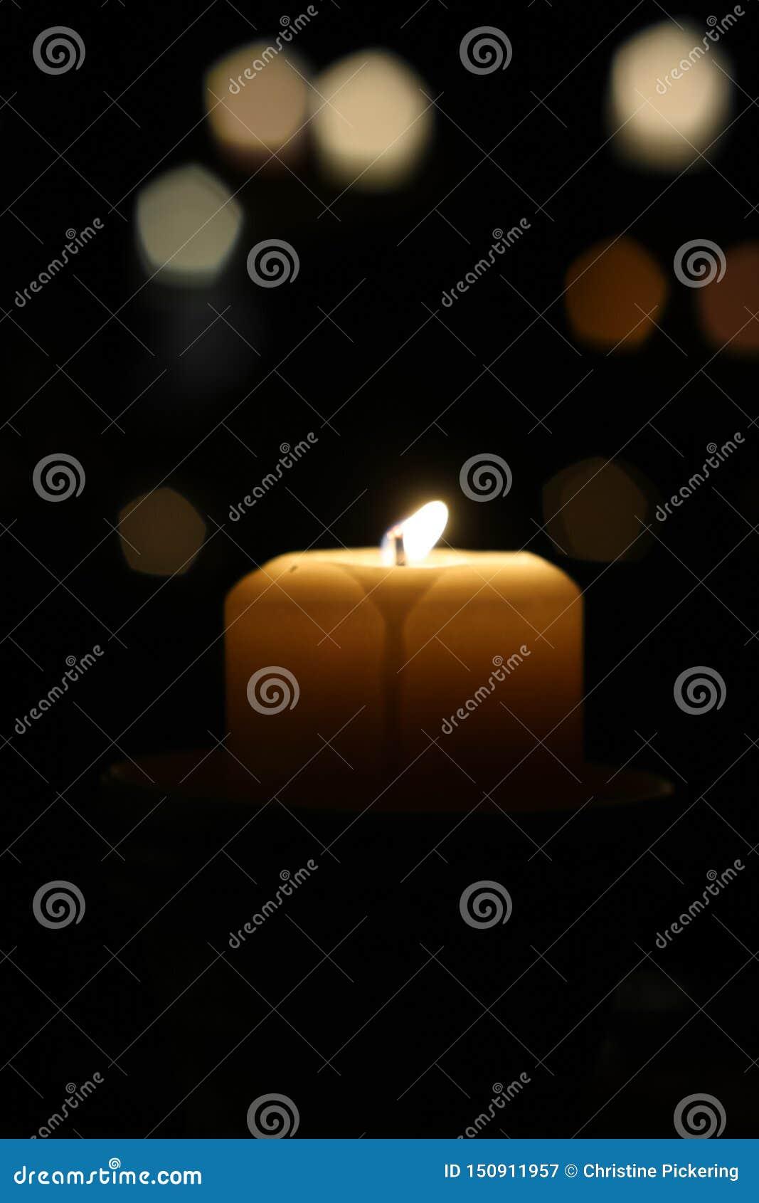 Eine Kerze flackert hell auf einer dunklen Nacht
