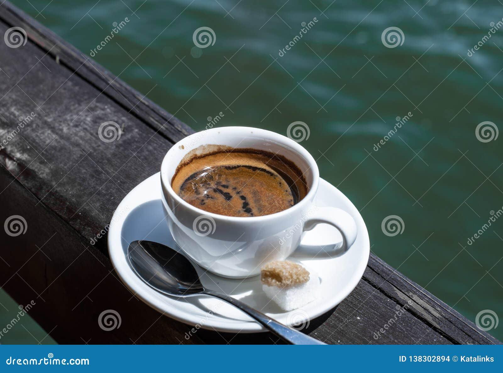 Eine kleine weiße Porzellanespressoschale auf einer Untertasse mit einem Teelöffel und zwei Stücken Zucker