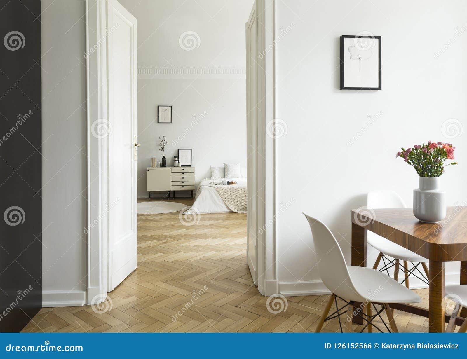 Eine Langstreckenansicht von einem Esszimmer in ein Schlafzimmer in einer hohen Decke flach Einfarbiger weißer Innenraum mit Fisc