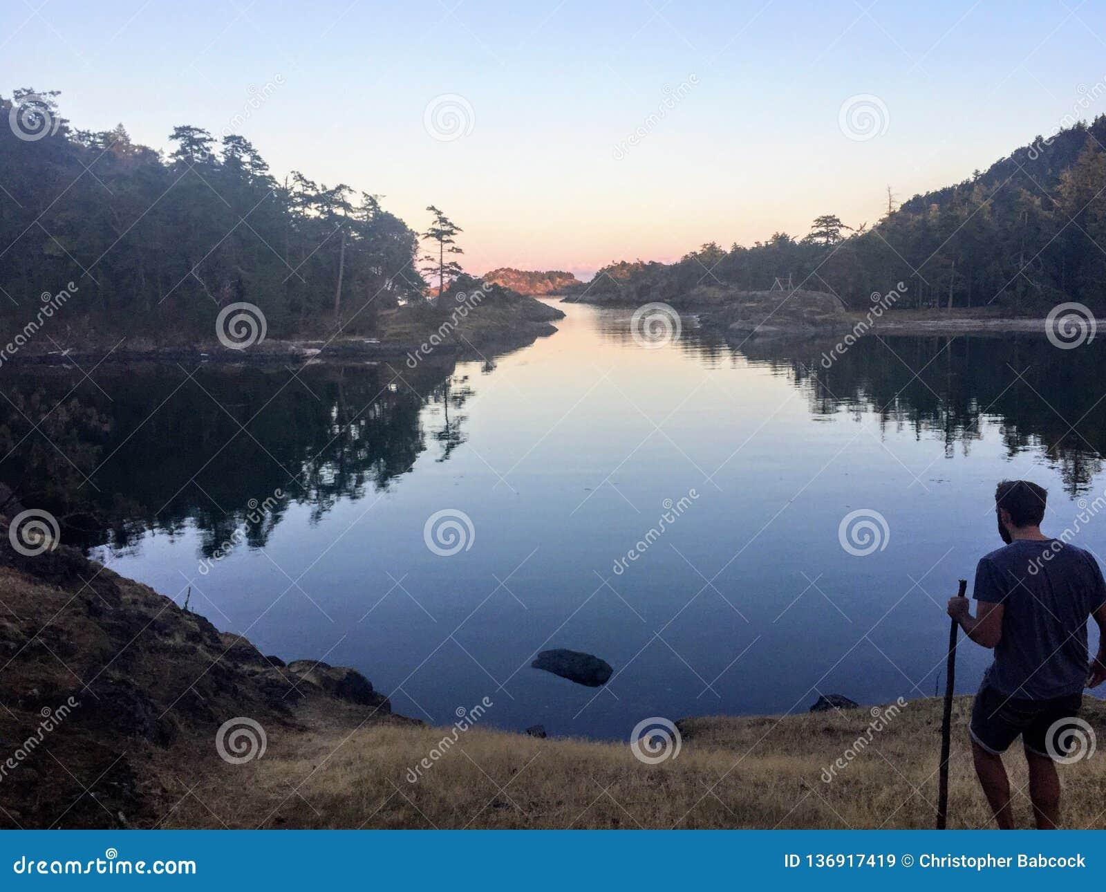 Eine Mannstellung entlang den Ufern der Golf-Inseln im Britisch-Columbia, Kanada, denkend und erwägen
