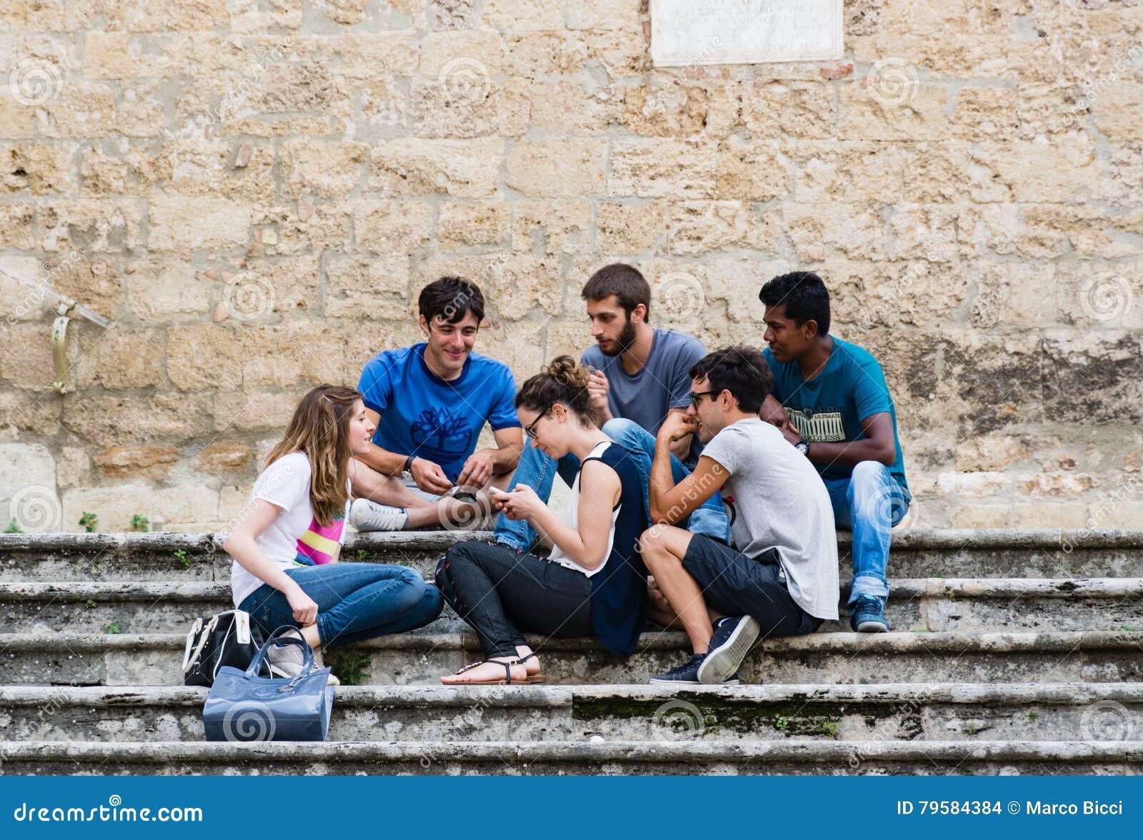 Eine multiethnische Gruppe Kerle, die Spaß plaudernd auf der Treppe O haben
