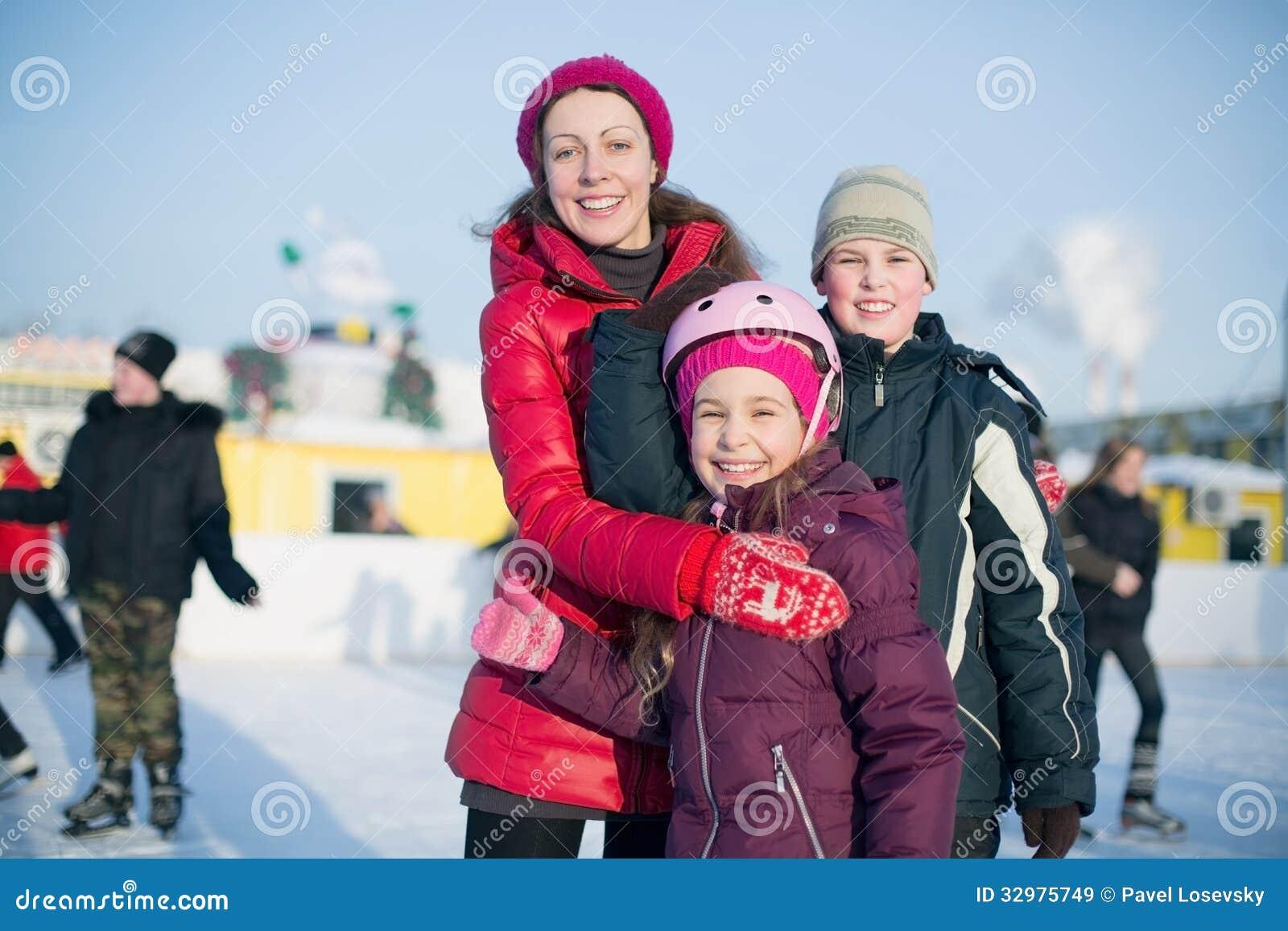 Eine Mutter mit zwei Kindern, die auf der Eisbahn im Freien stehen