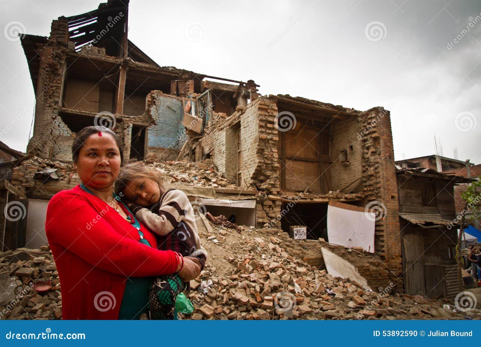 Eine Mutter und ein Kind außerhalb eines Erdbebens ruinierten Haus in Bhaktap