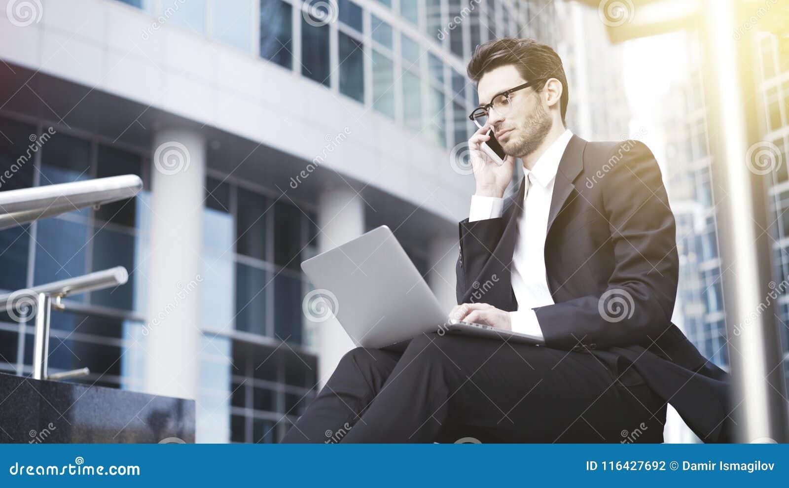 Eine Nahaufnahme des jungen hübschen Geschäftsmannes mit dem Laptop, der einen Anruf hat