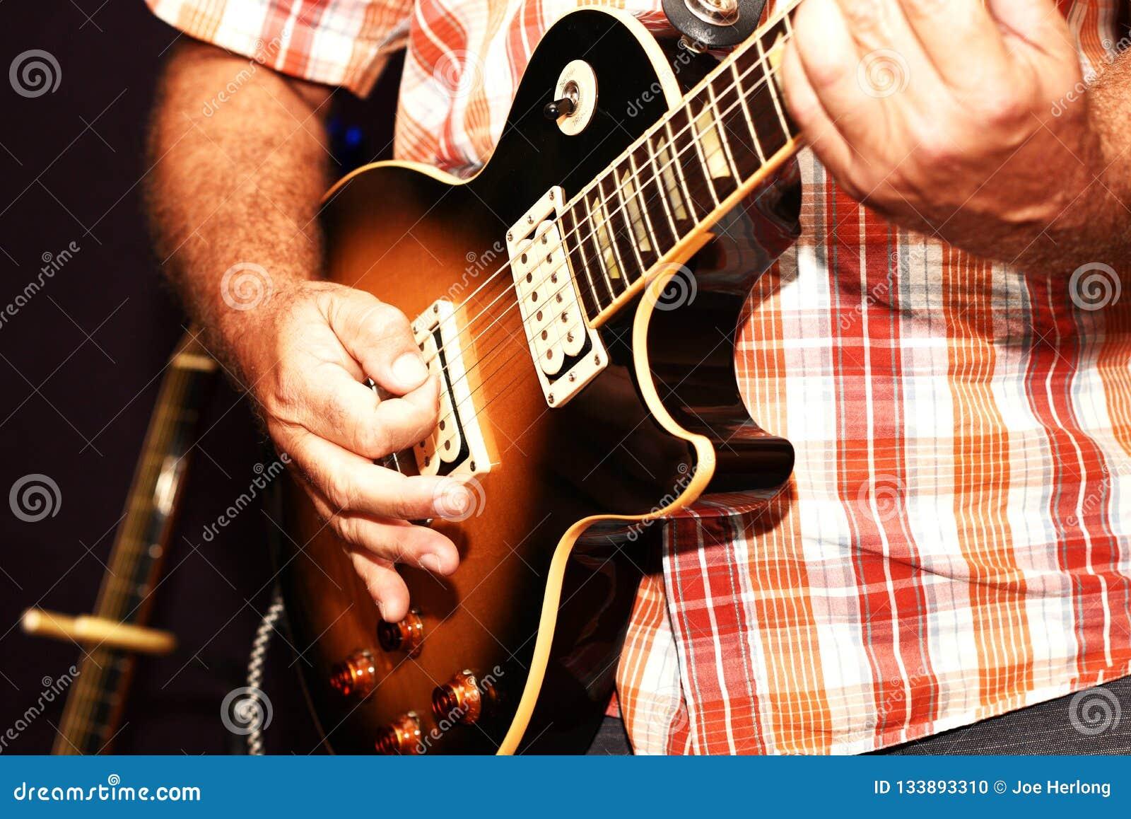 Eine Nahaufnahme eines Mannes, der eine E-Gitarre spielt