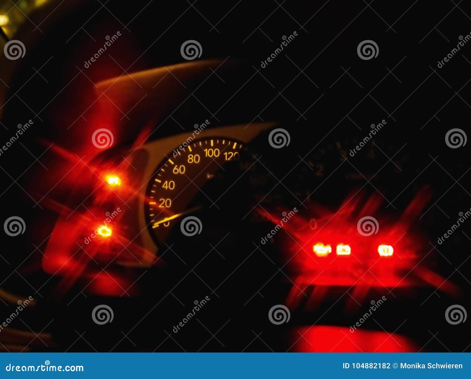 Eine Nahaufnahme von einem Geschwindigkeitsmesser eines Auto innight, mit dem Blinken von roten Lampen
