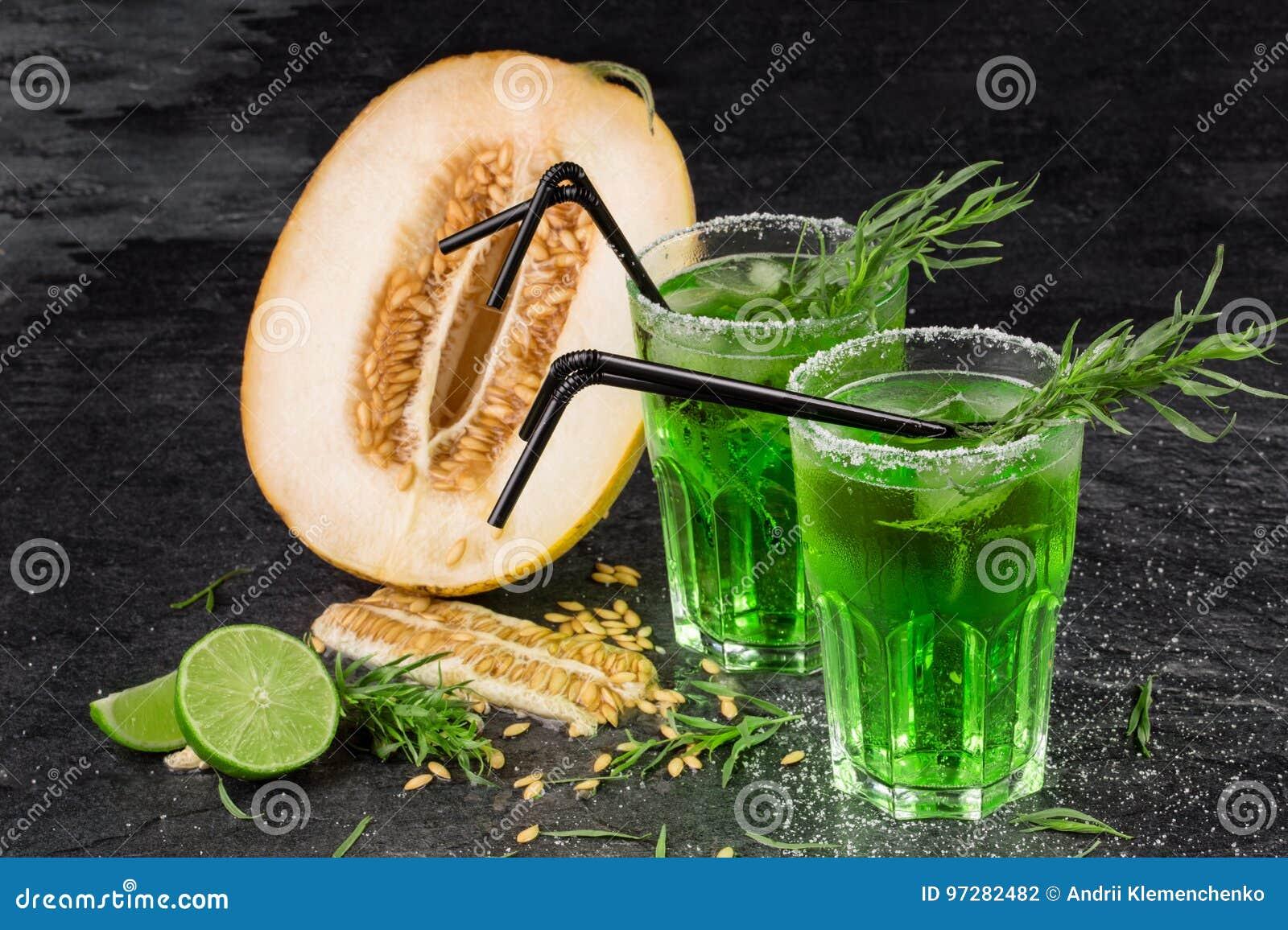 Eine Nahaufnahme von exotischen Früchten Grüne Alkoholcocktails mit Strohen Schneiden Sie Melone Estragond-clips und frischer Kal