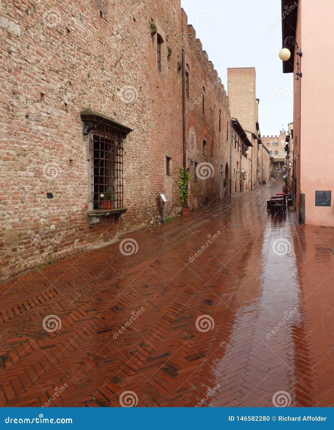 Eine nass Ziegelsteinstraße in Certaldo Italien