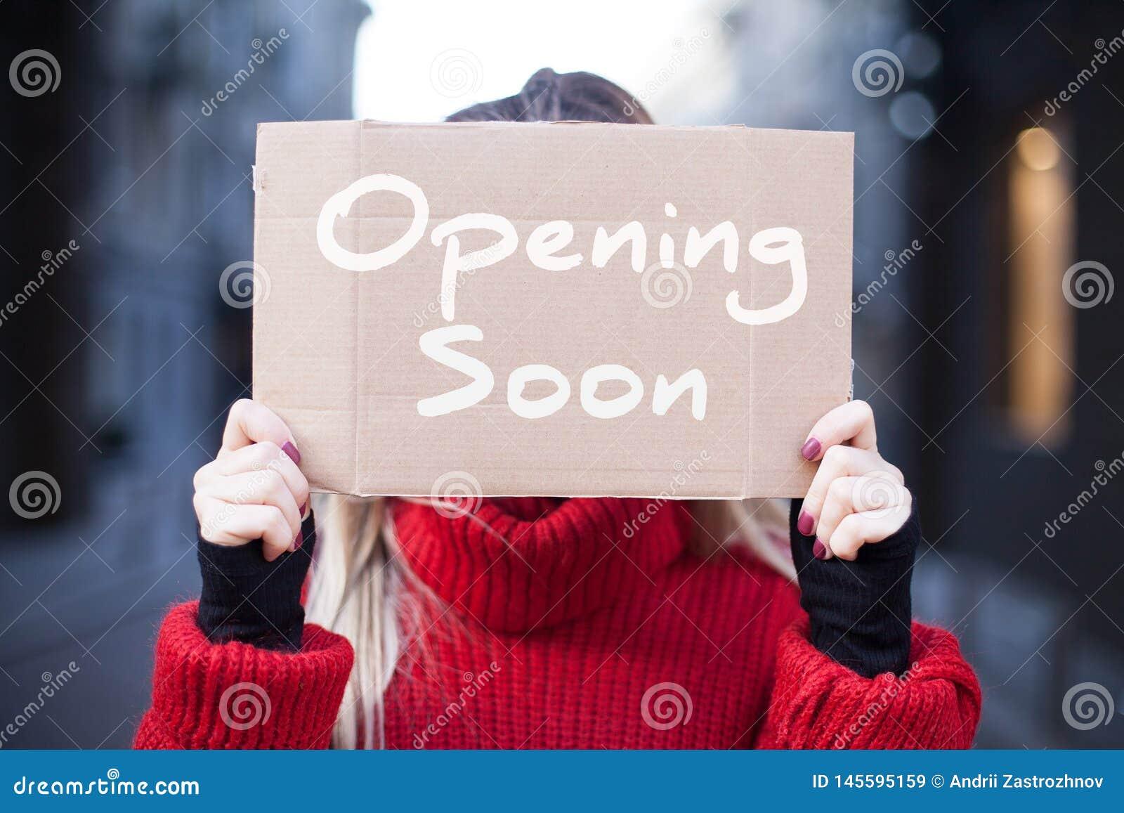 Eine Papptablettennahaufnahme mit der Aufschrift 'bald öffnend 'in den Händen einer jungen Frau in einer roten Strickjacke