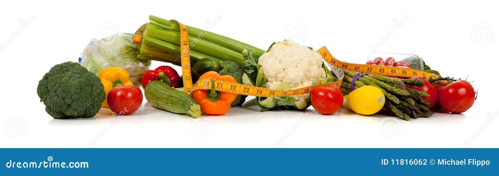Eine Reihe des Gemüses und ein Bandmaß auf Weiß