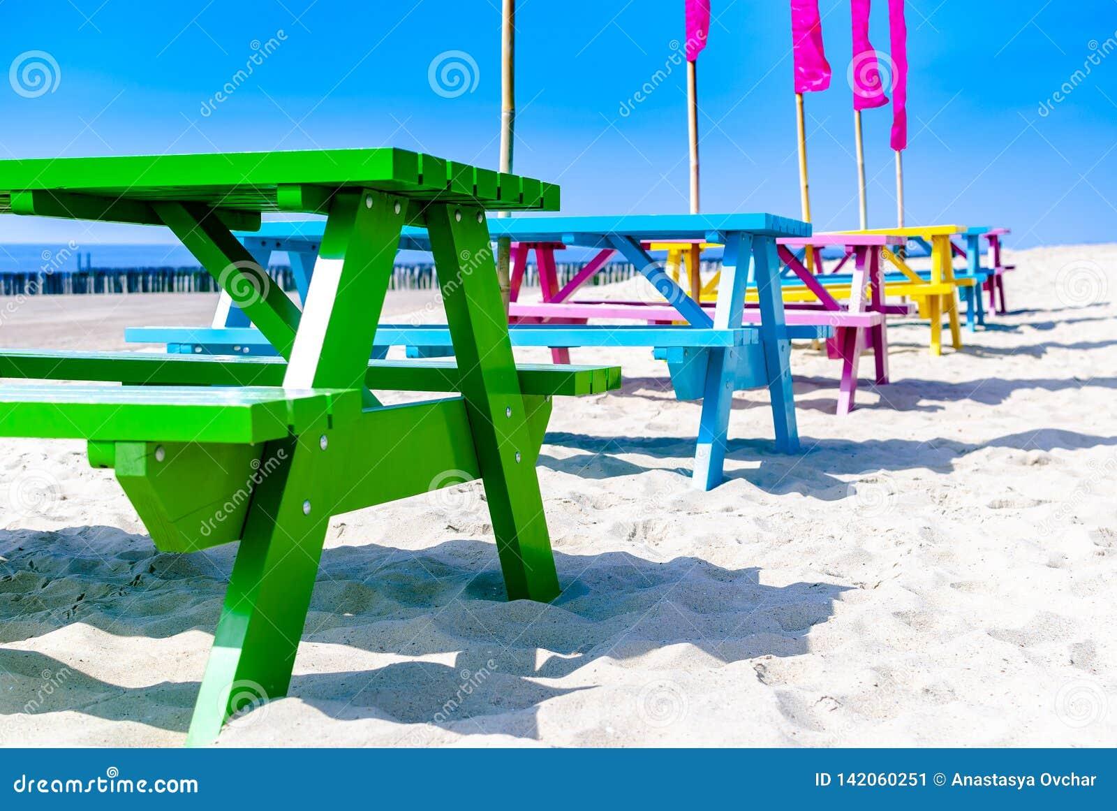 Eine Reihe von bunten Holztischen auf einem leeren Strand Seashells gestalten auf Sandhintergrund Ferienmieten rückzug Frühling N