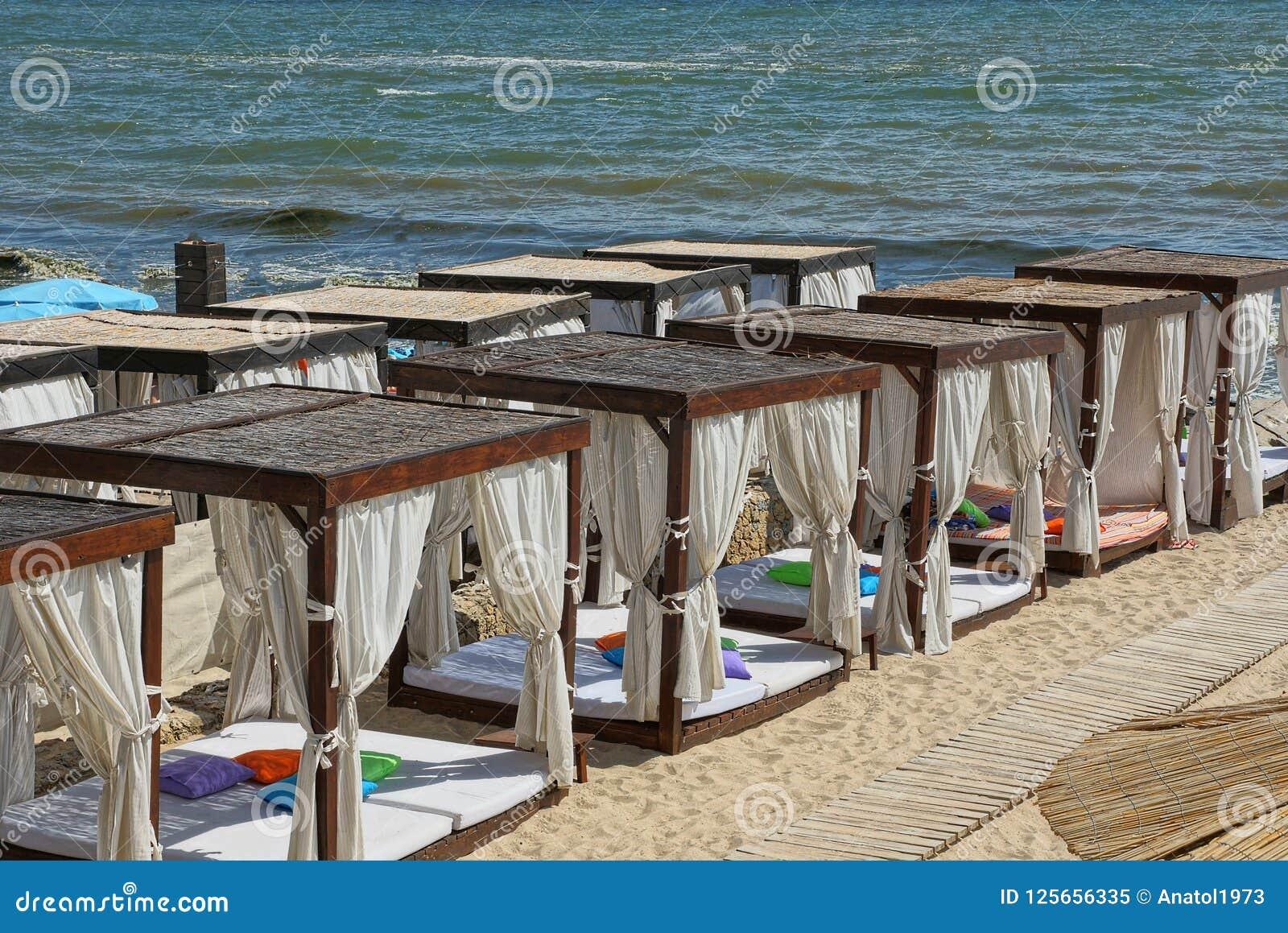 Eine Reihe von offenen Pavillons des Brauns mit weißen Vorhängen auf dem Strandsand nahe dem Meer