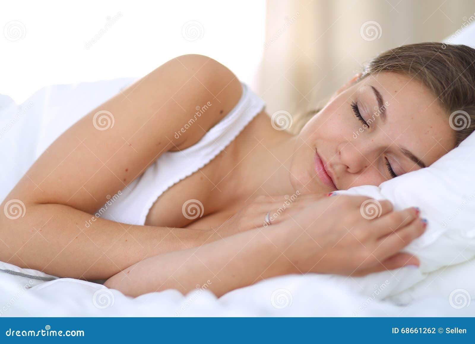 Eine schöne junge Frau bequem und, die himmlisch im Bett liegt