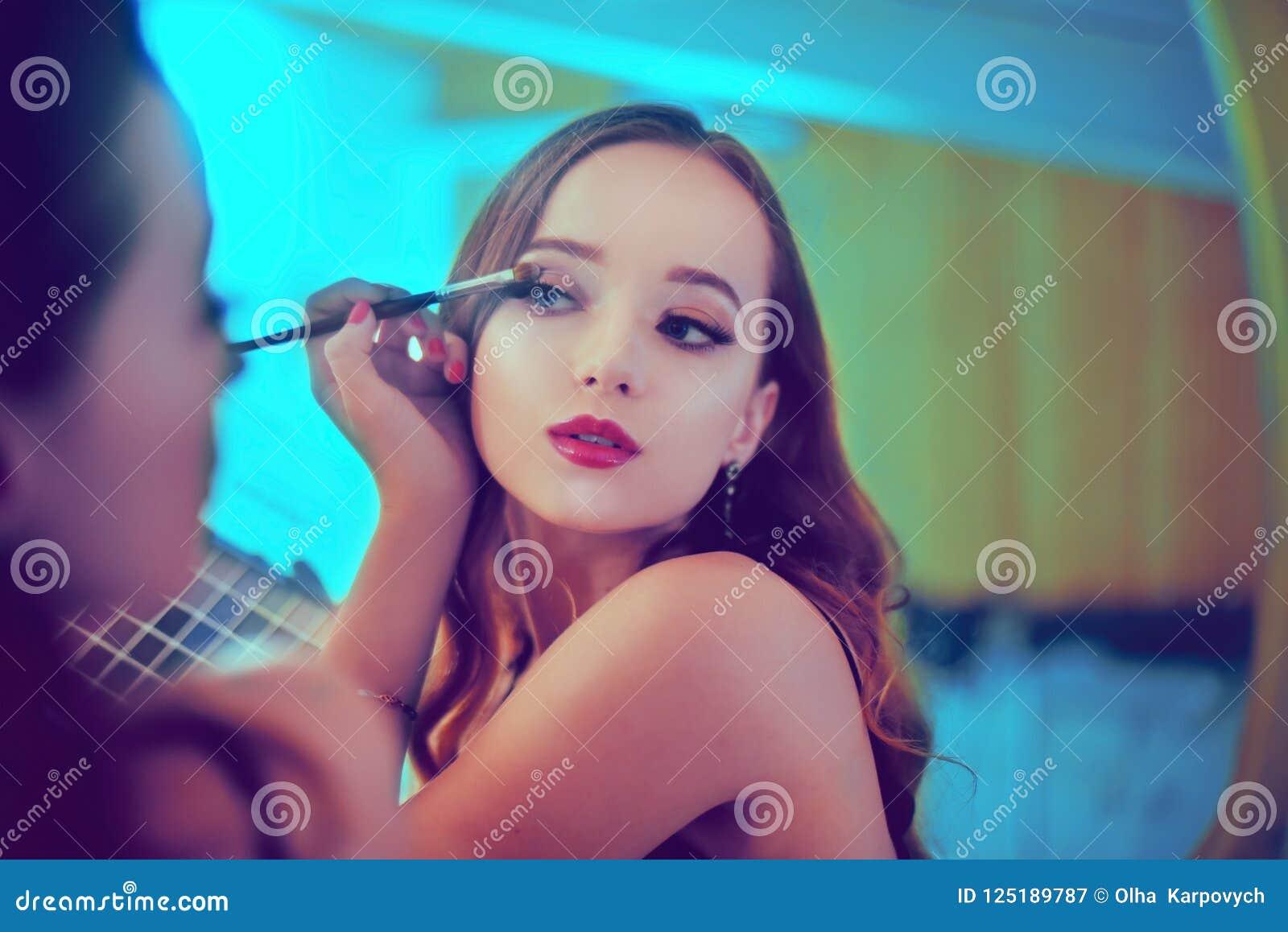 Eine schöne junge Frau tut sich eine Umarbeitung Mädchen mit cerly dem Haar, das Make-up unter Verwendung Bürste und Lidschattens