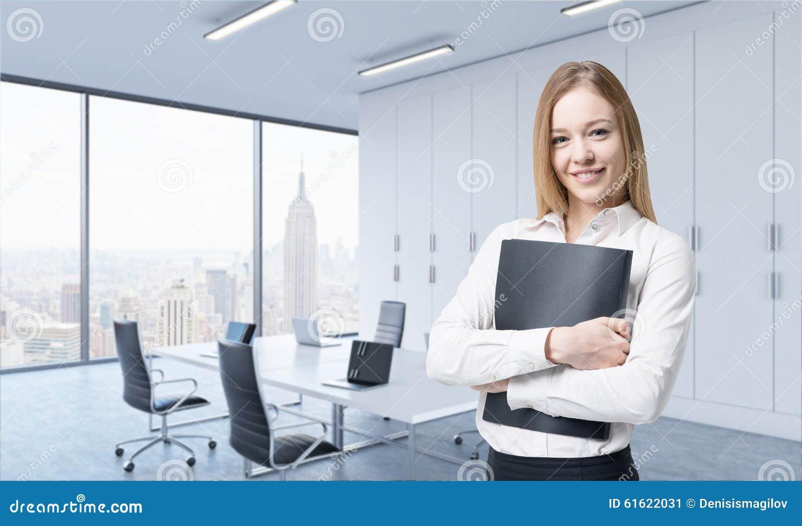 Eine schöne lächelnde Frau hält einen schwarzen Dokumentenordner im modernen panoramischen Büro