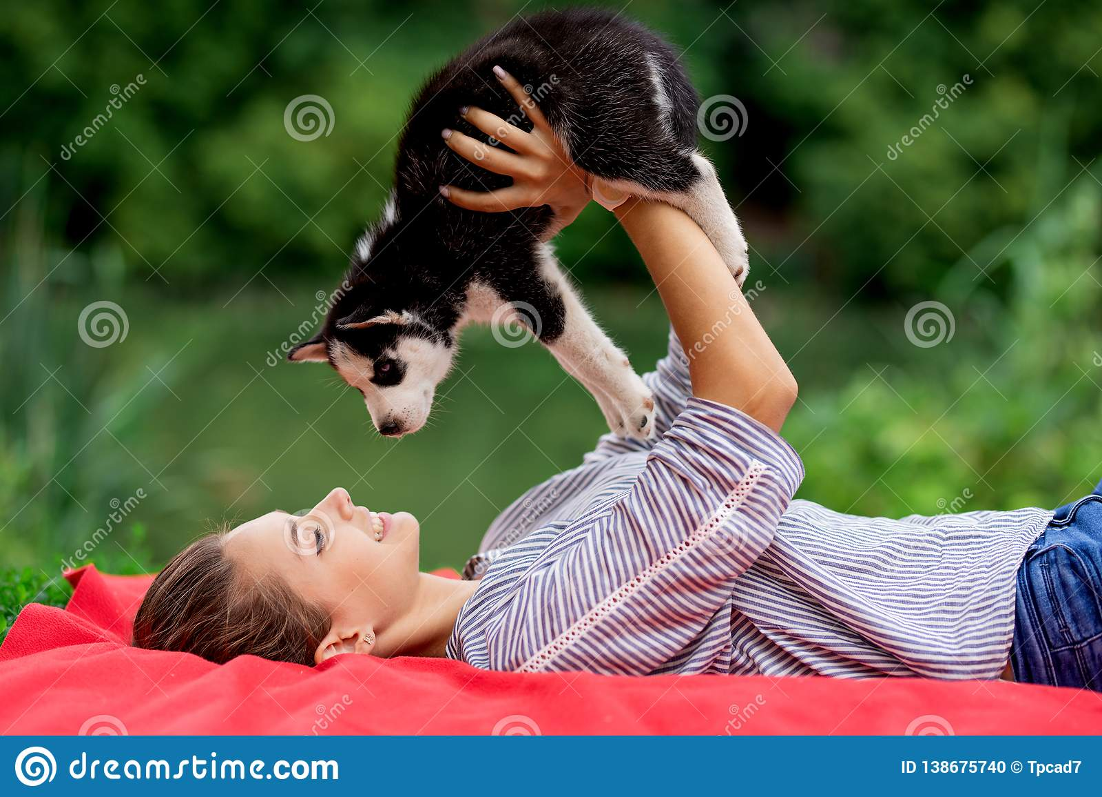 Eine schöne lächelnde Frau mit einem Pferdeschwanz und dem Tragen eines gestreiften Hemdes spielt mit einem süßen heiseren Welpen