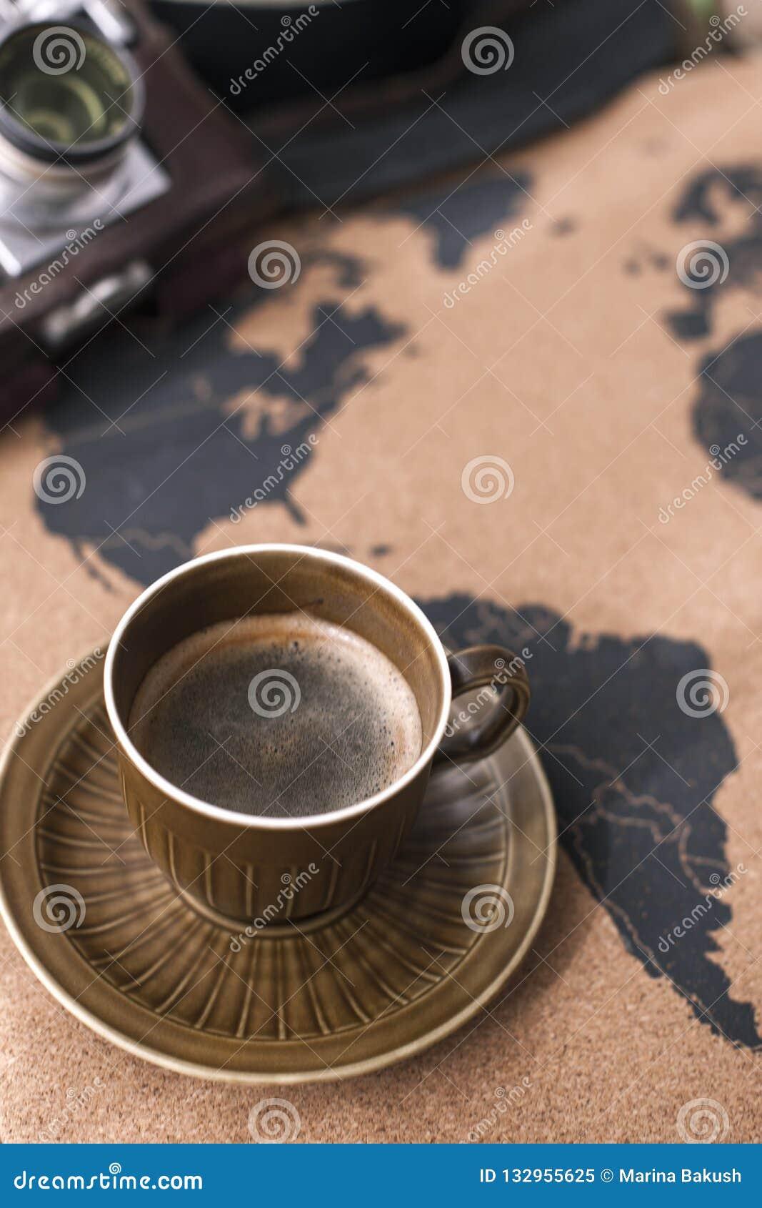 Eine Schale wohlriechender Kaffee auf der Karte, einer alten Kamera und einem Weg p